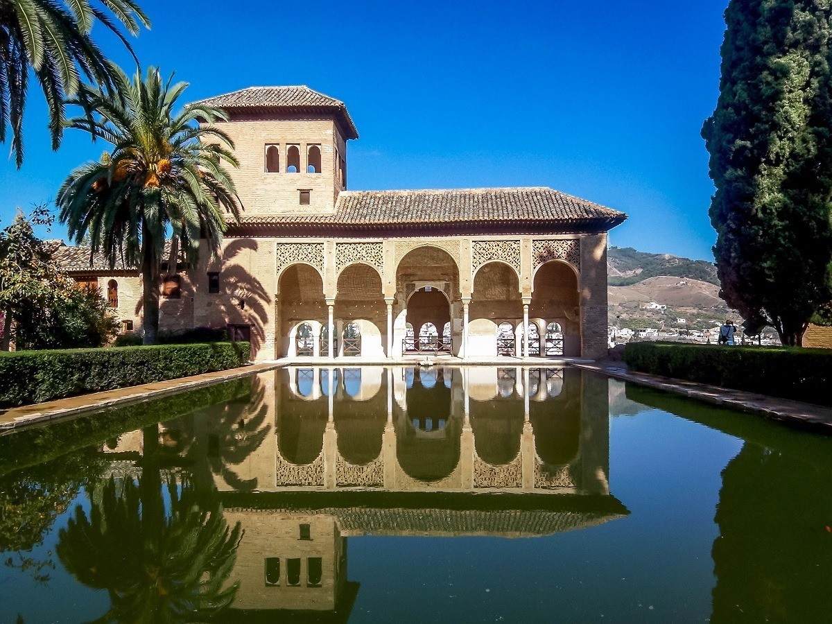 Building with arched doorways over reflecting pool