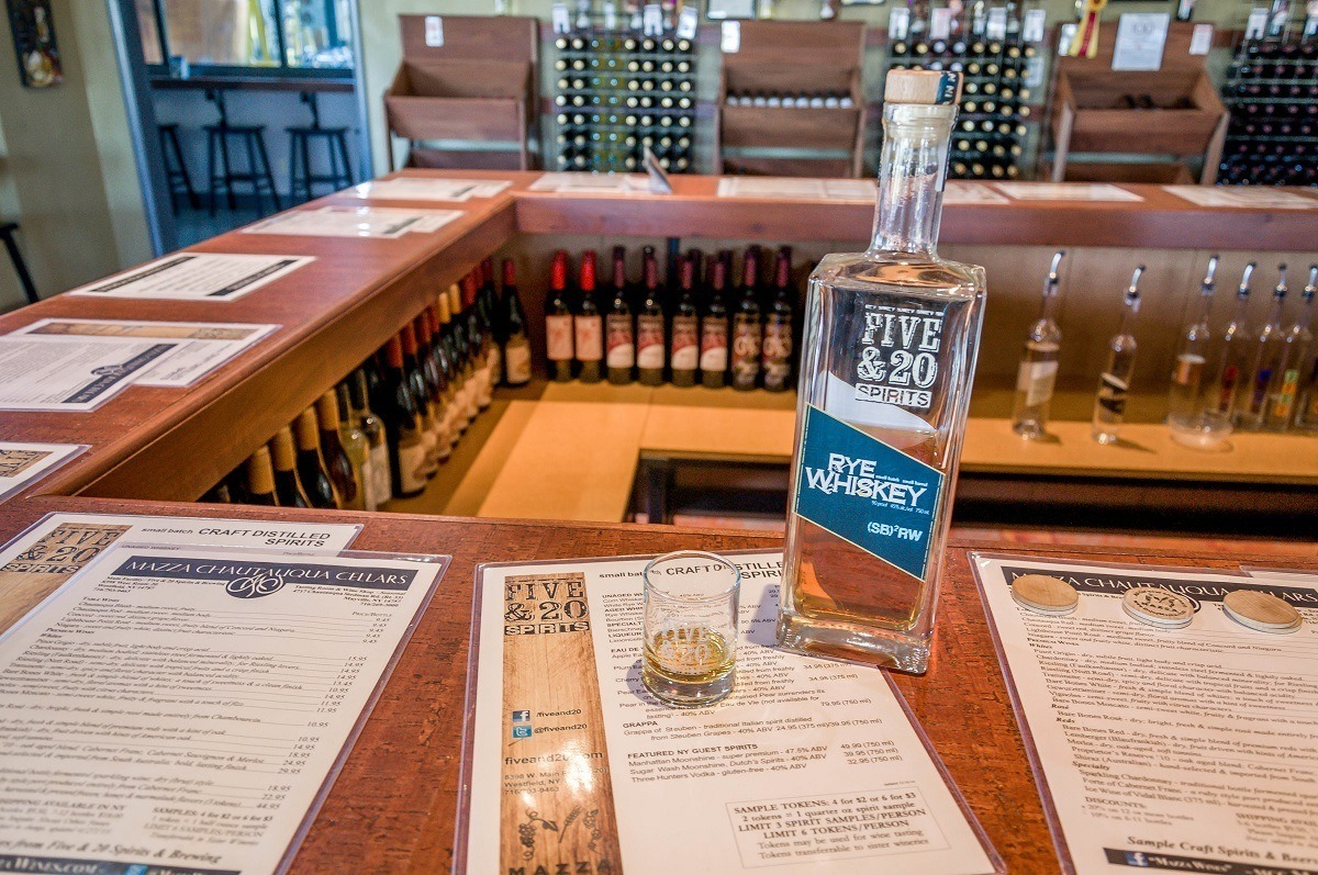 Rye whiskey bottle and shot glass on a bar with menus