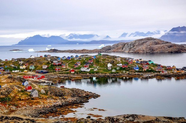 Colorful houses along a coastline with snow-covered mountains