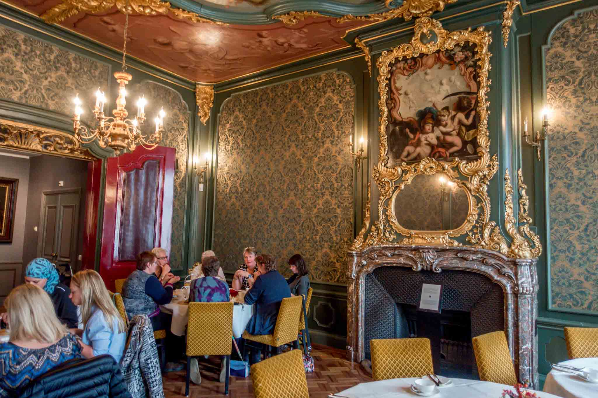 People in tea room decorated with brocade wallpaper and ornate fireplace