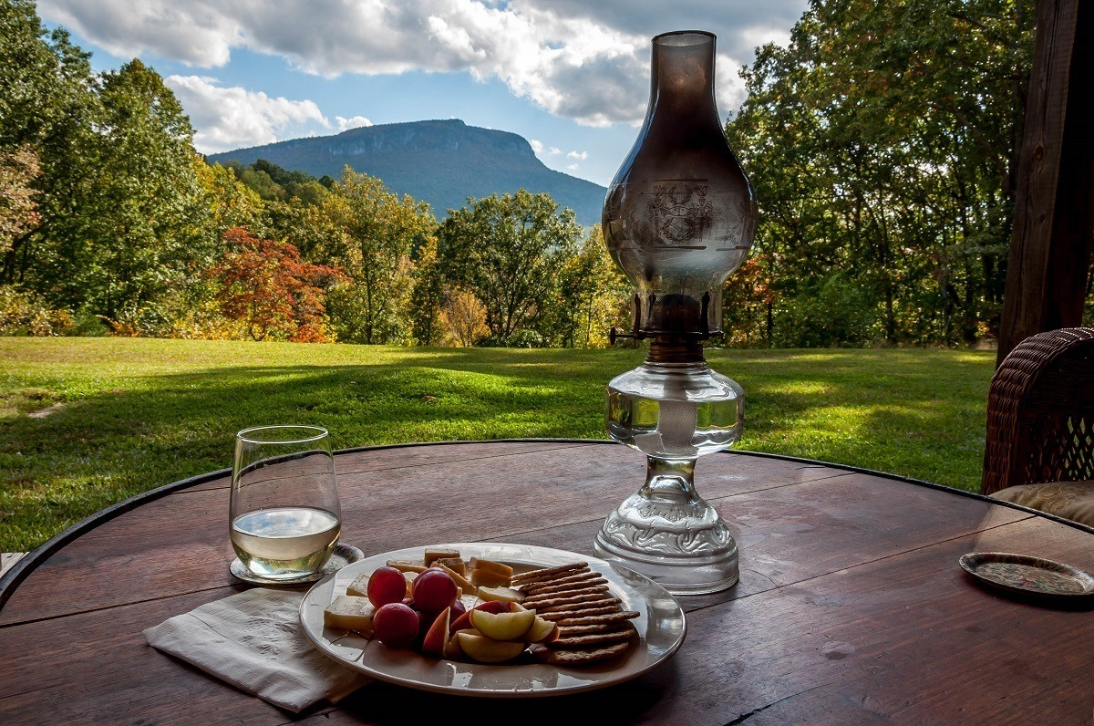 Wine and cheese on a table with a view of fall foliage