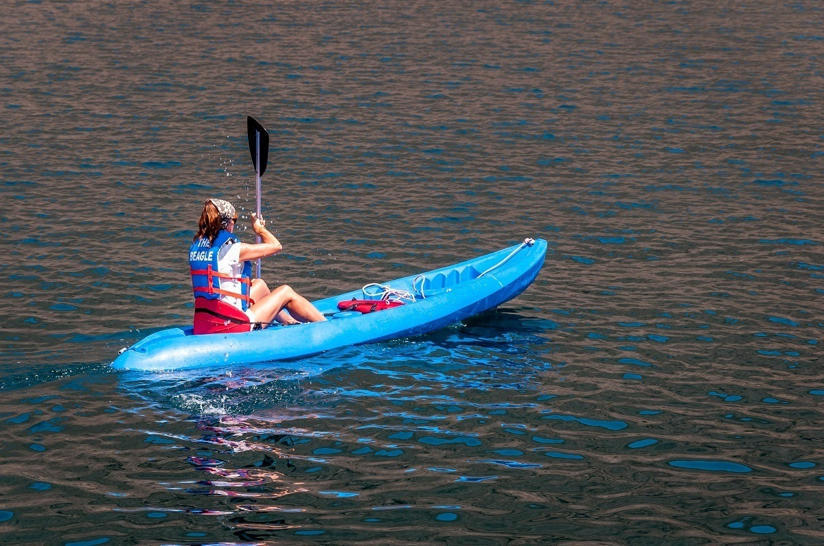 A woman in a blue sea kayak during a Galapagos cruise