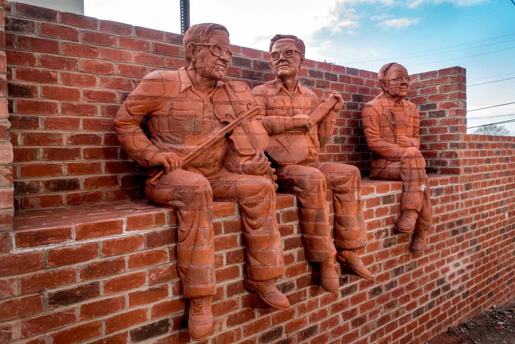 Brick sculptures of musicians sitting on a wall