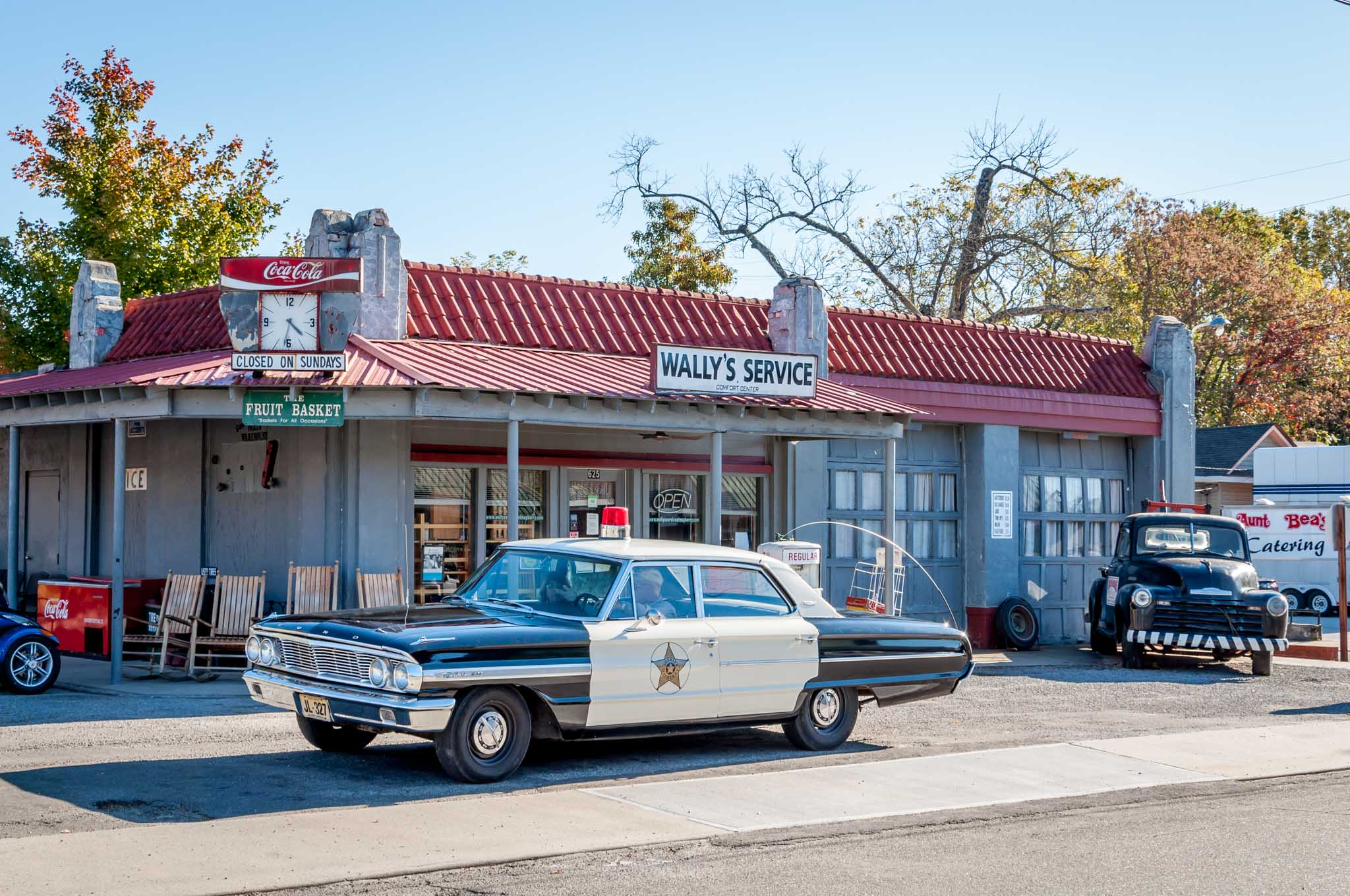 Old fashioned police car in front of Wally's Service station