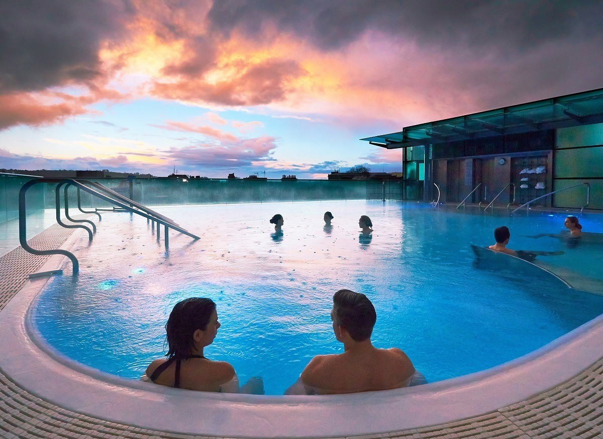 The open-air rooftop pool at the Thermae Bath Spa at sunset