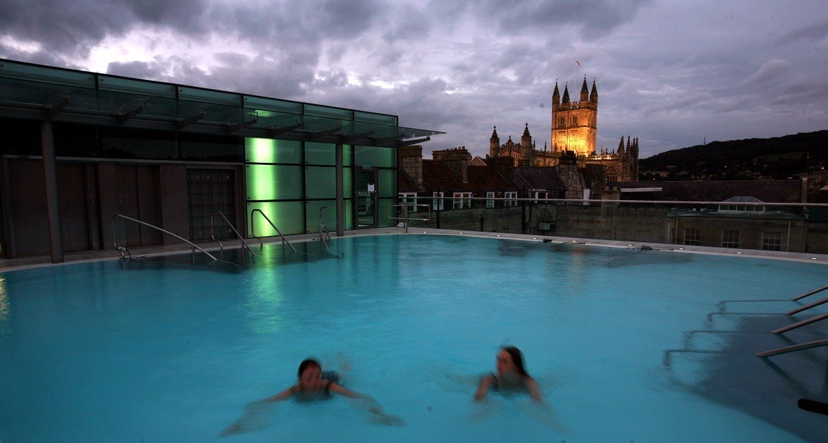 Women swimming in the rooftop pool at twilight