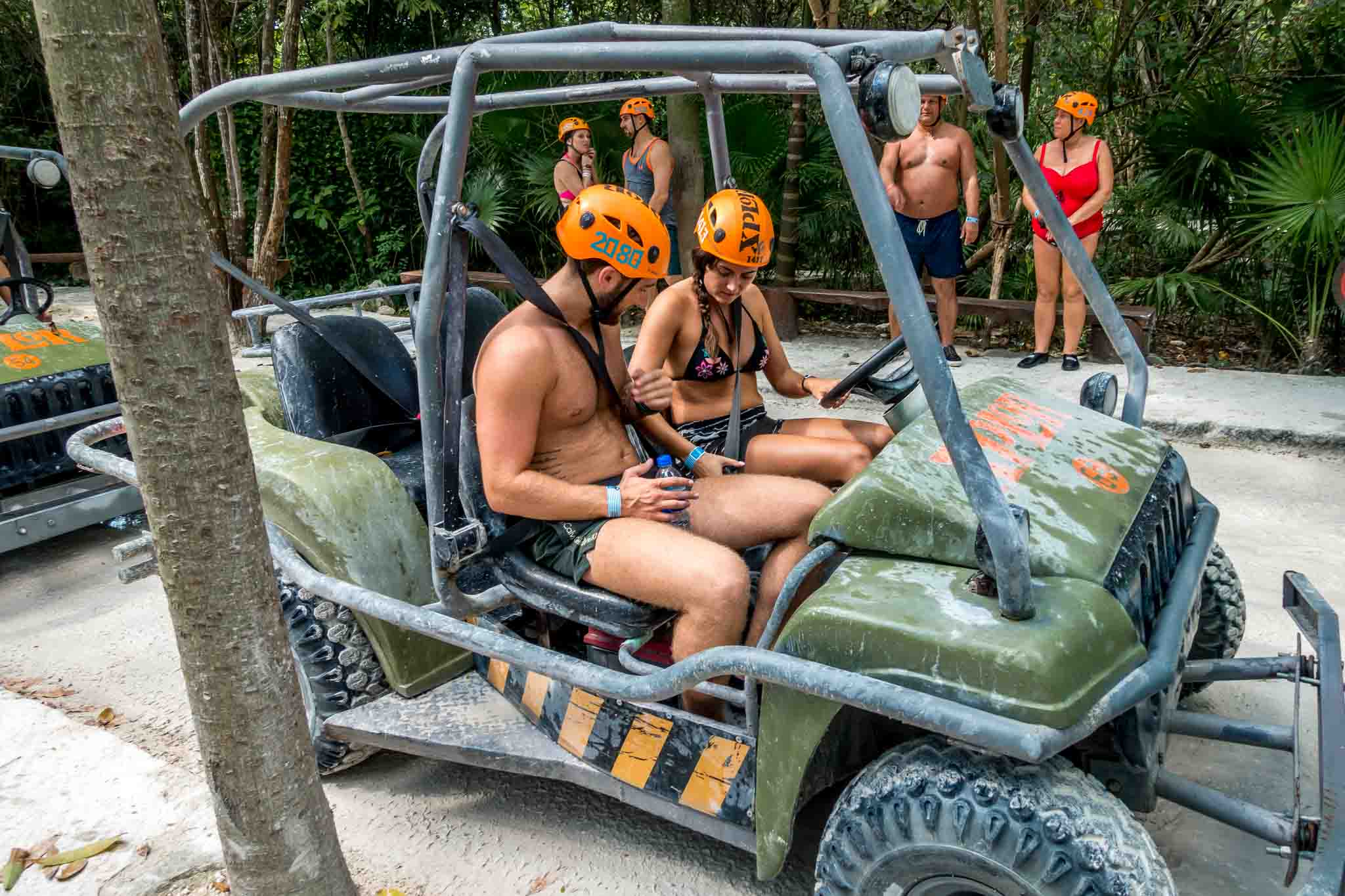 People fastening seatbelts in their amphibious vehicle