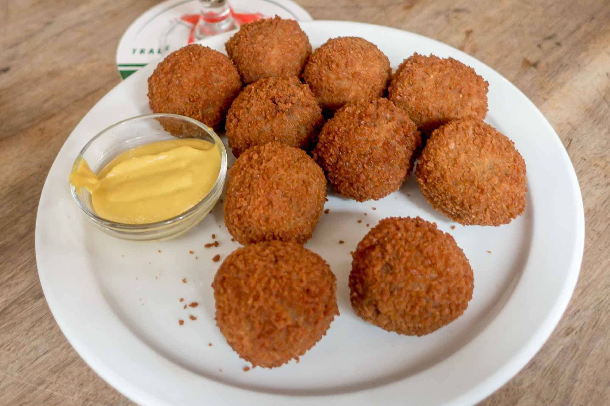 Fried balls of bitterballen with mustard on a plate