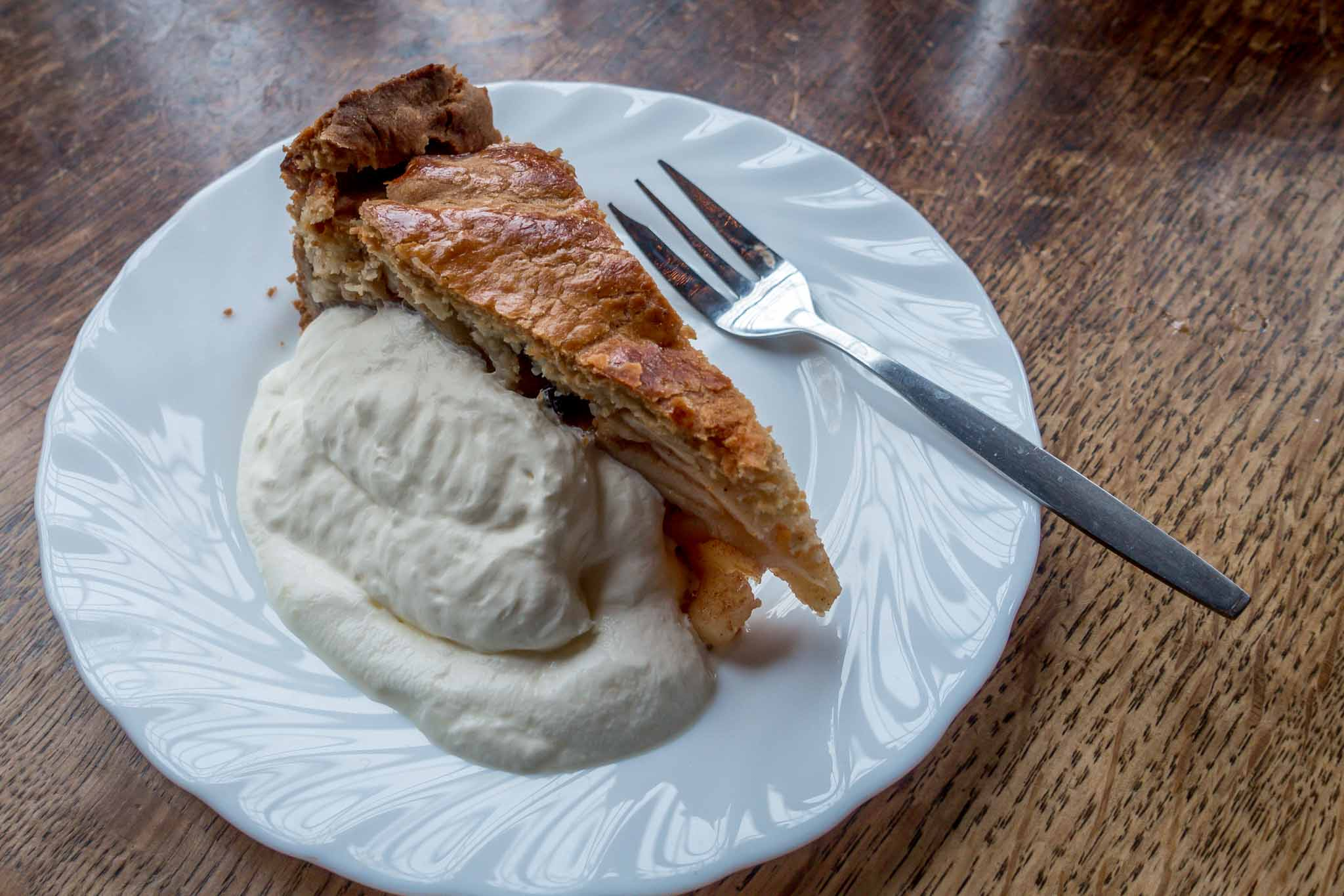 Dutch apple pie with whipped cream and fork
