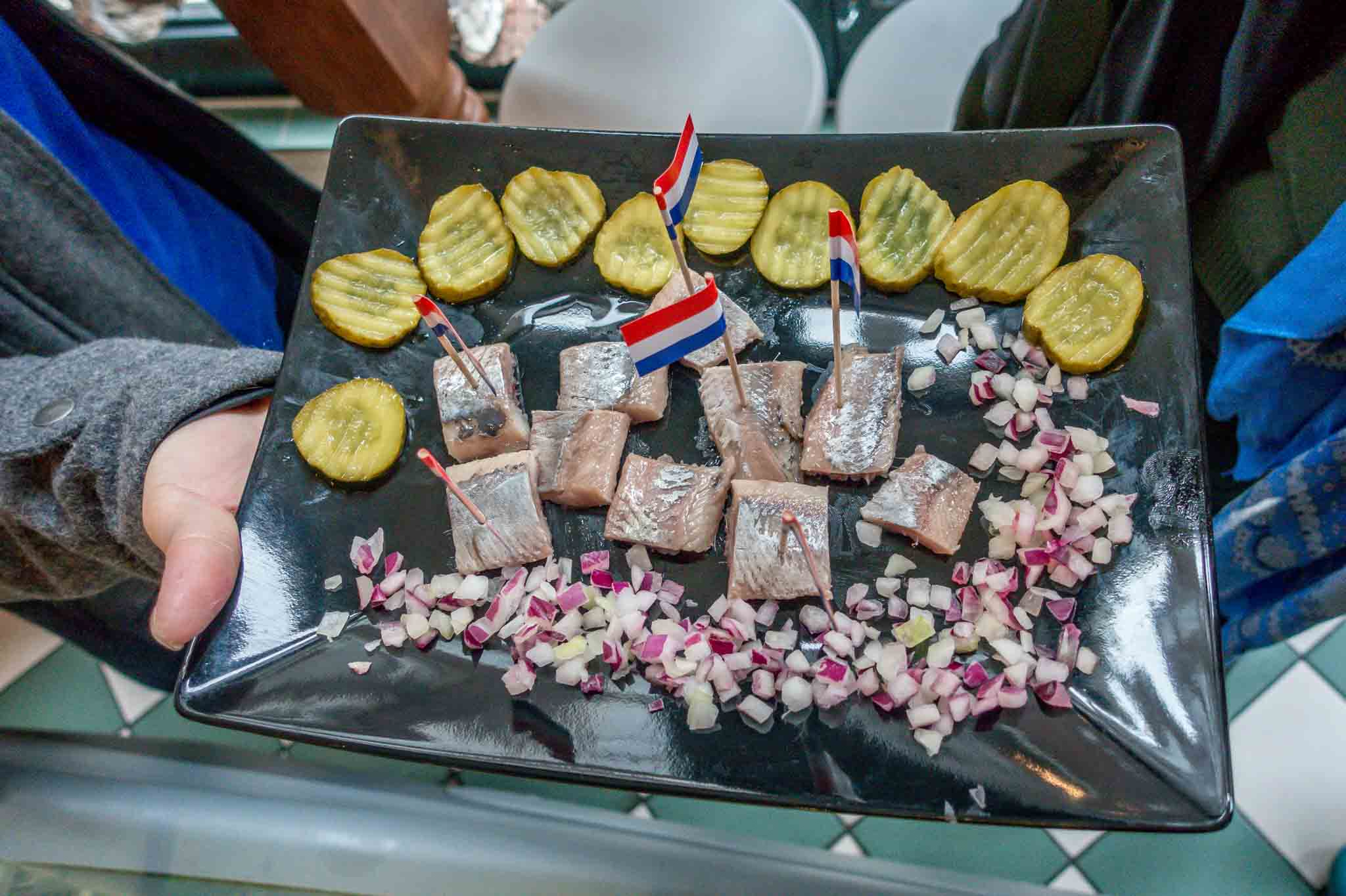 Pickled herring with onions and pickles on a platter