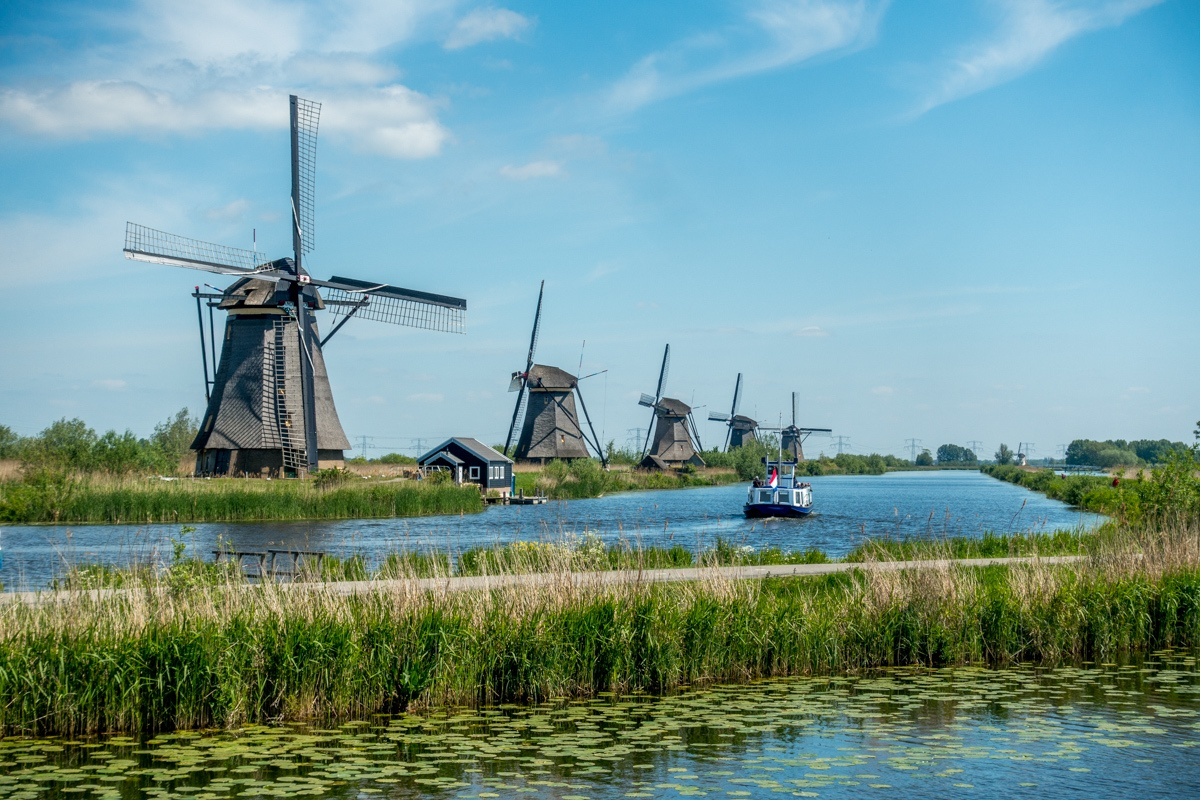 Five windmills with a boat passing by in the canal at Kinderdijk