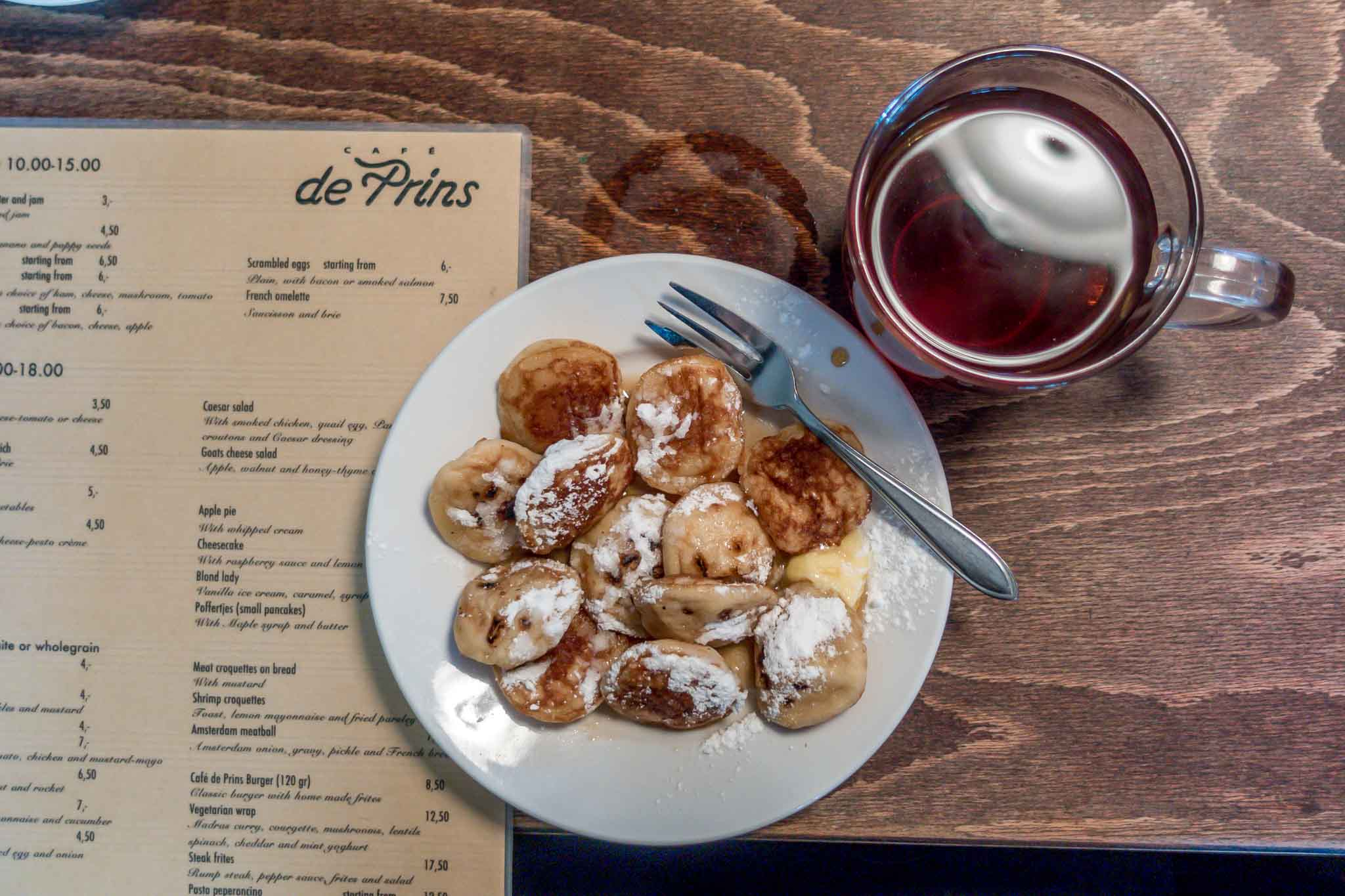 Plate of small puffy pancakes with a cup of tea and a menu