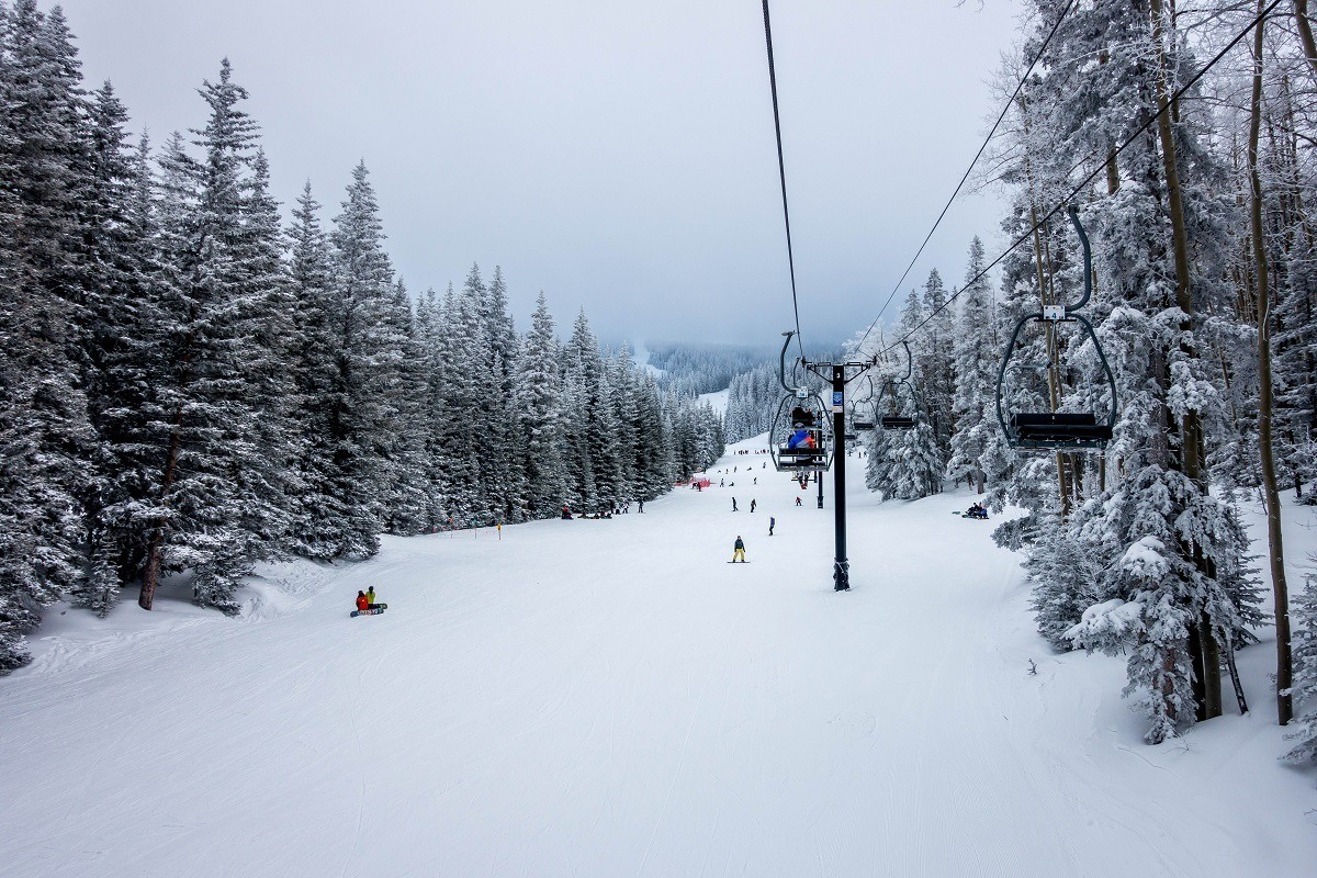 People skiing and snowboarding under the chair lift