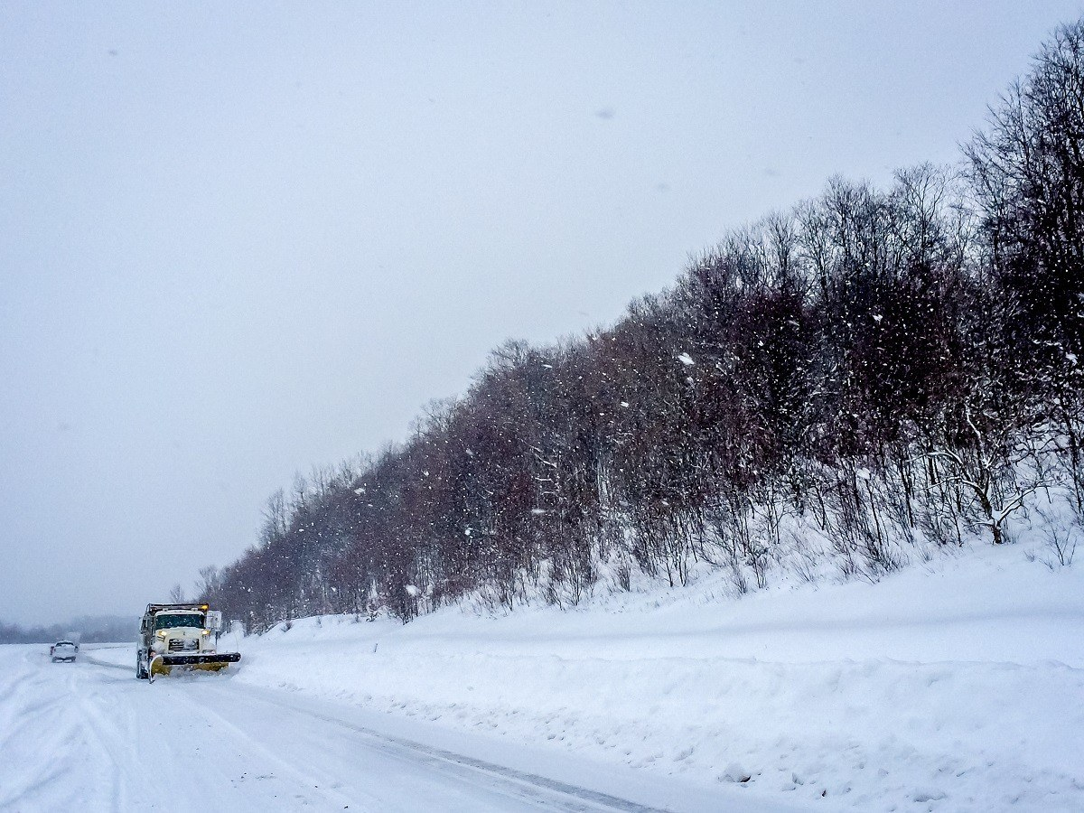 Snow plow driving on a snow-covered highway