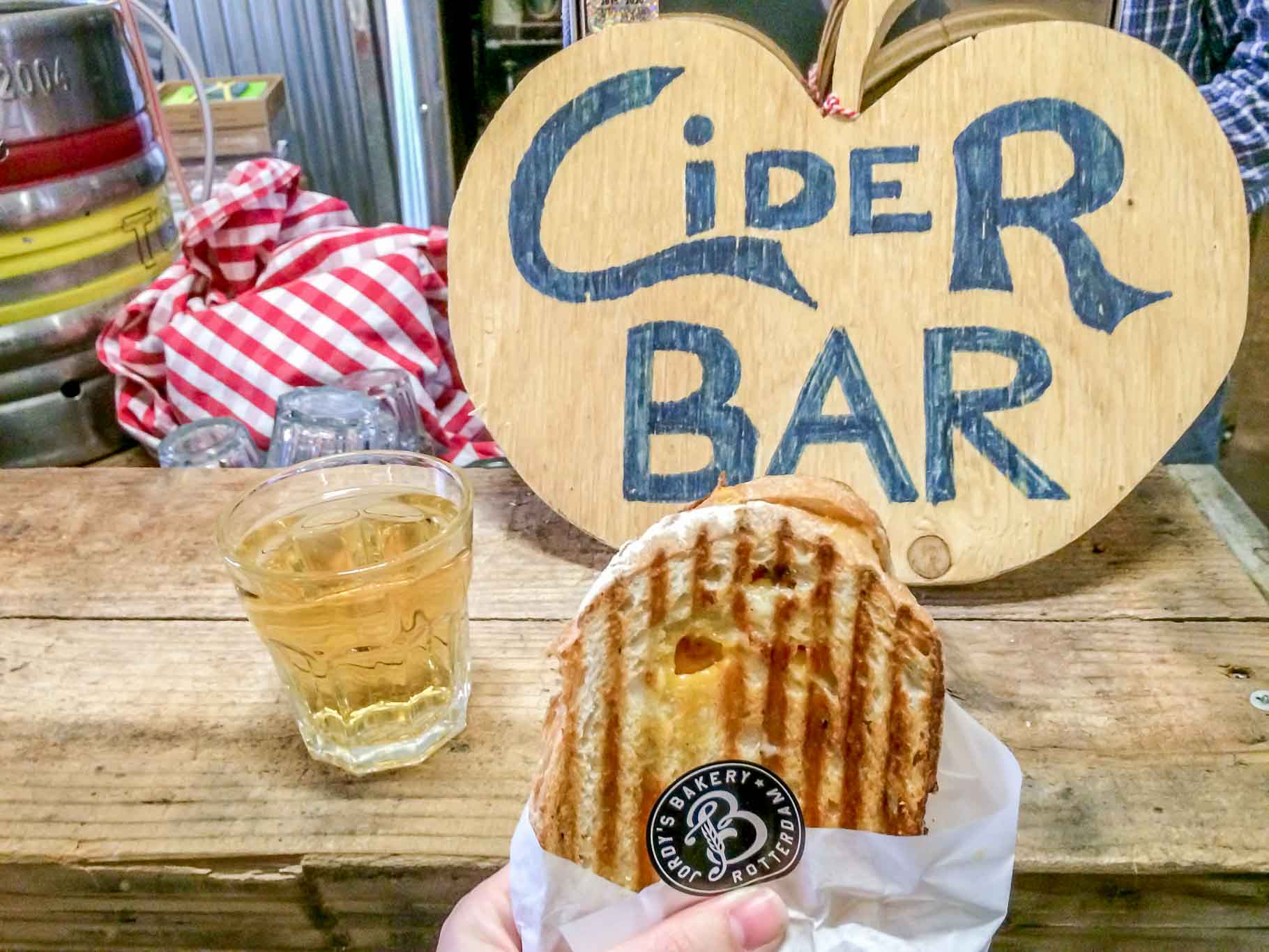"""""""Cider Bar"""" sign, sandwich, and drink on a table"""