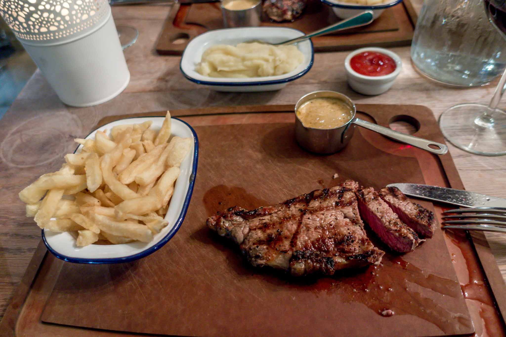 Sliced steak and French fries on a cutting board