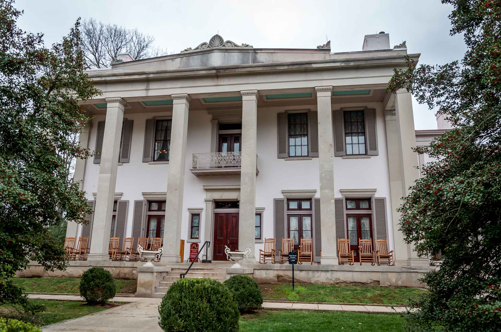 Columned Greek-Revival mansion with chairs on the front porch