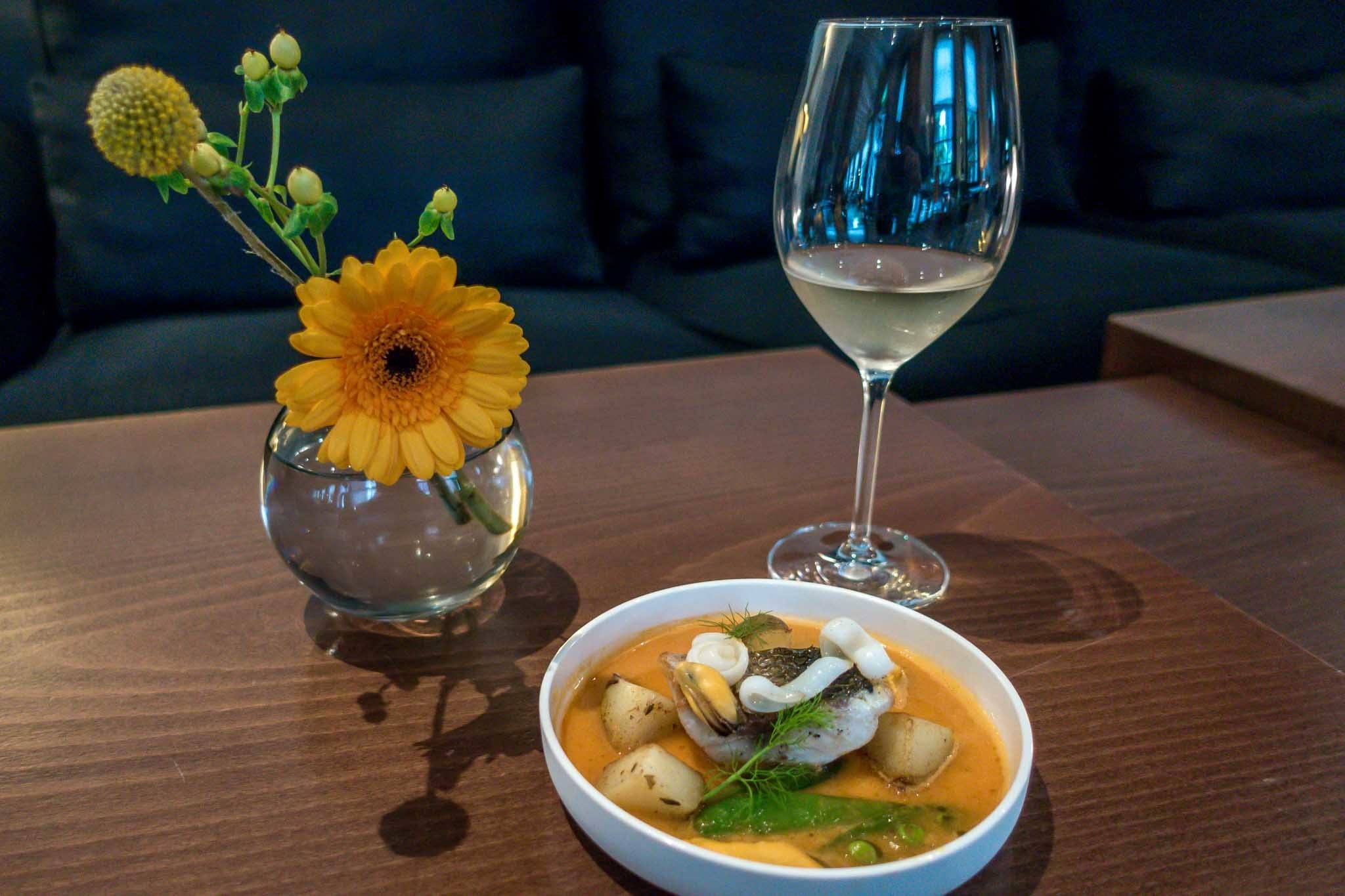 Seafood stew and wine on a table with a flower decoration