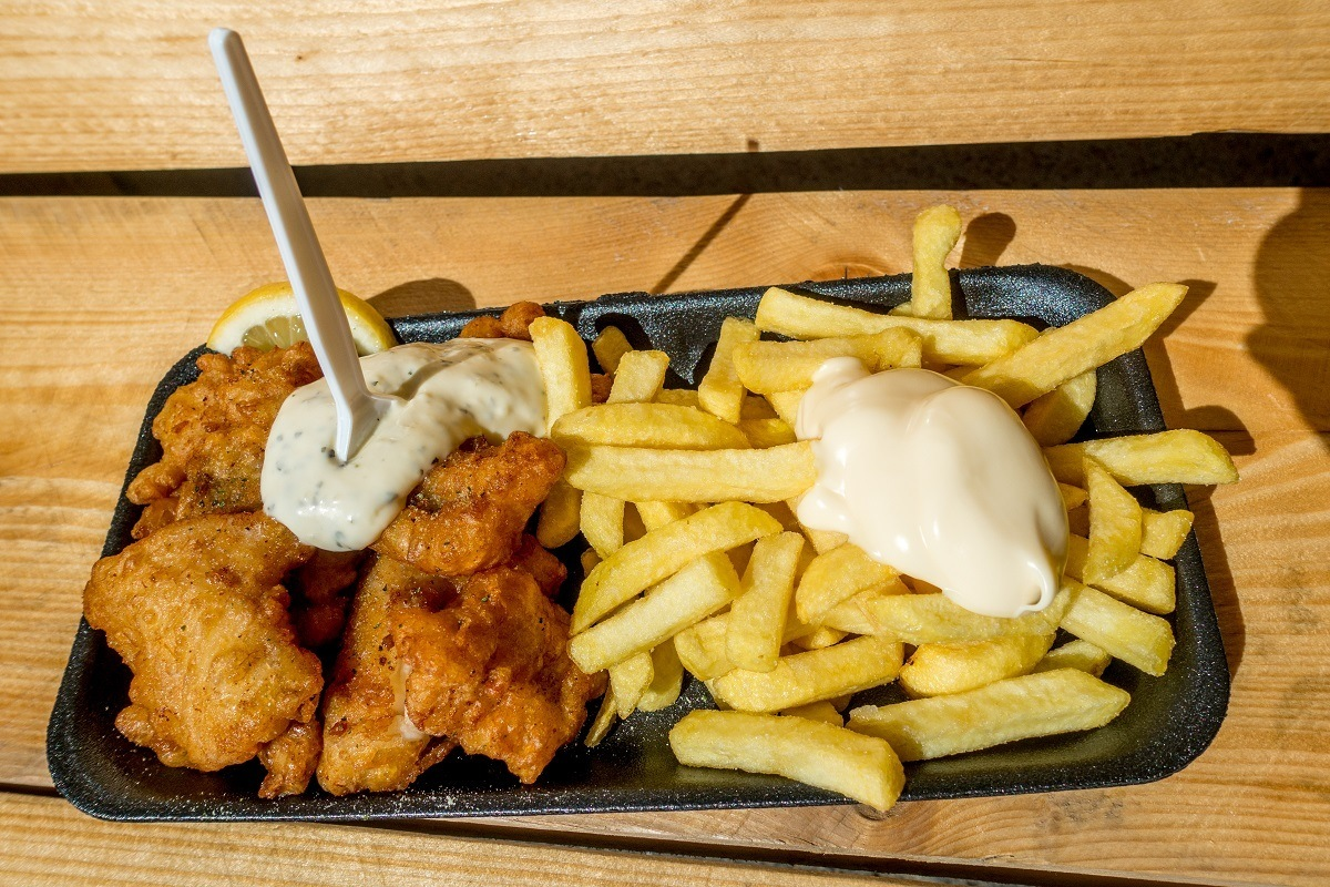 Fried cod with tartar sauce and French fries on a plate
