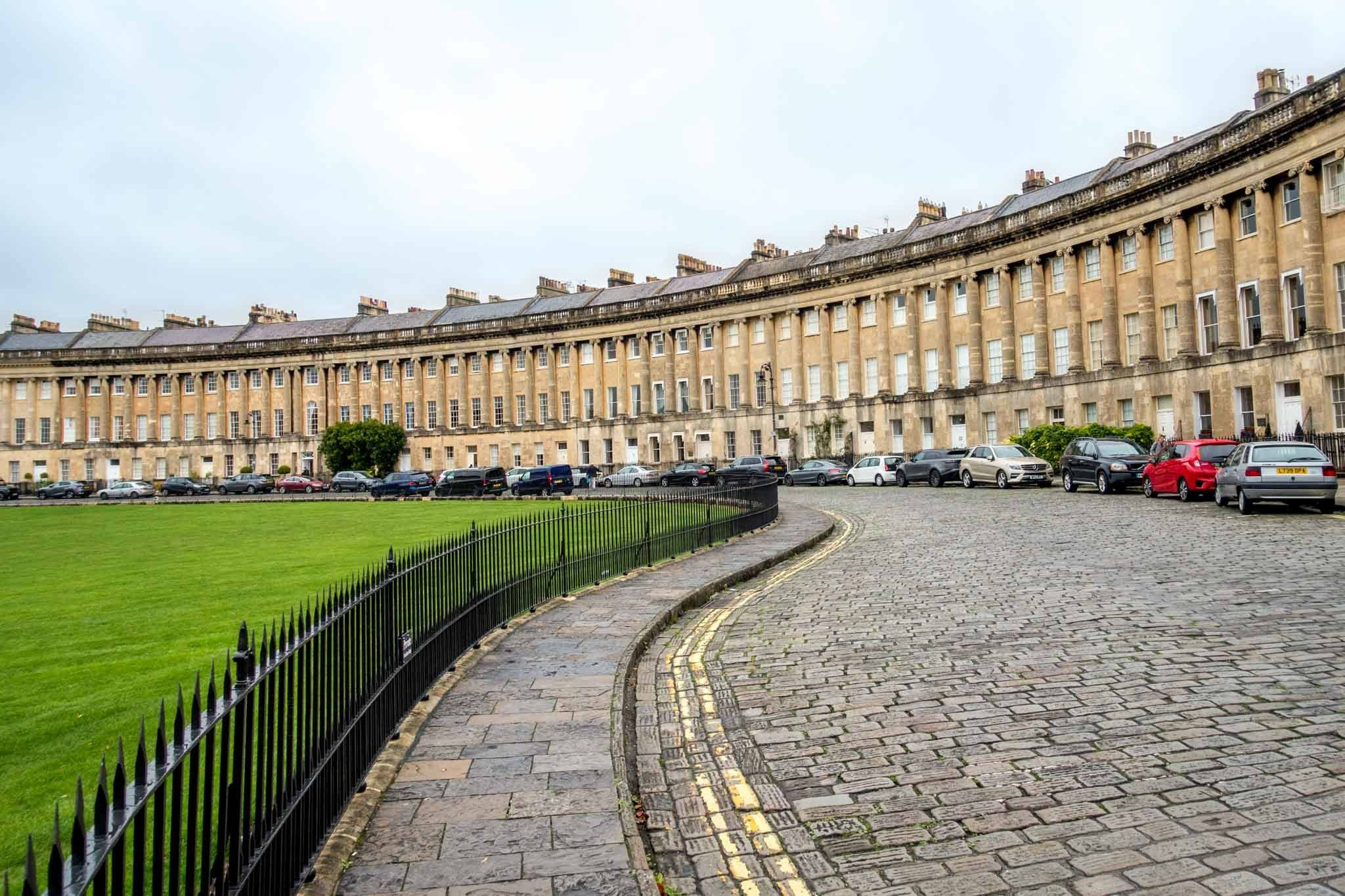 Curved row of Georgian houses with cars parked, the Royal Crescent