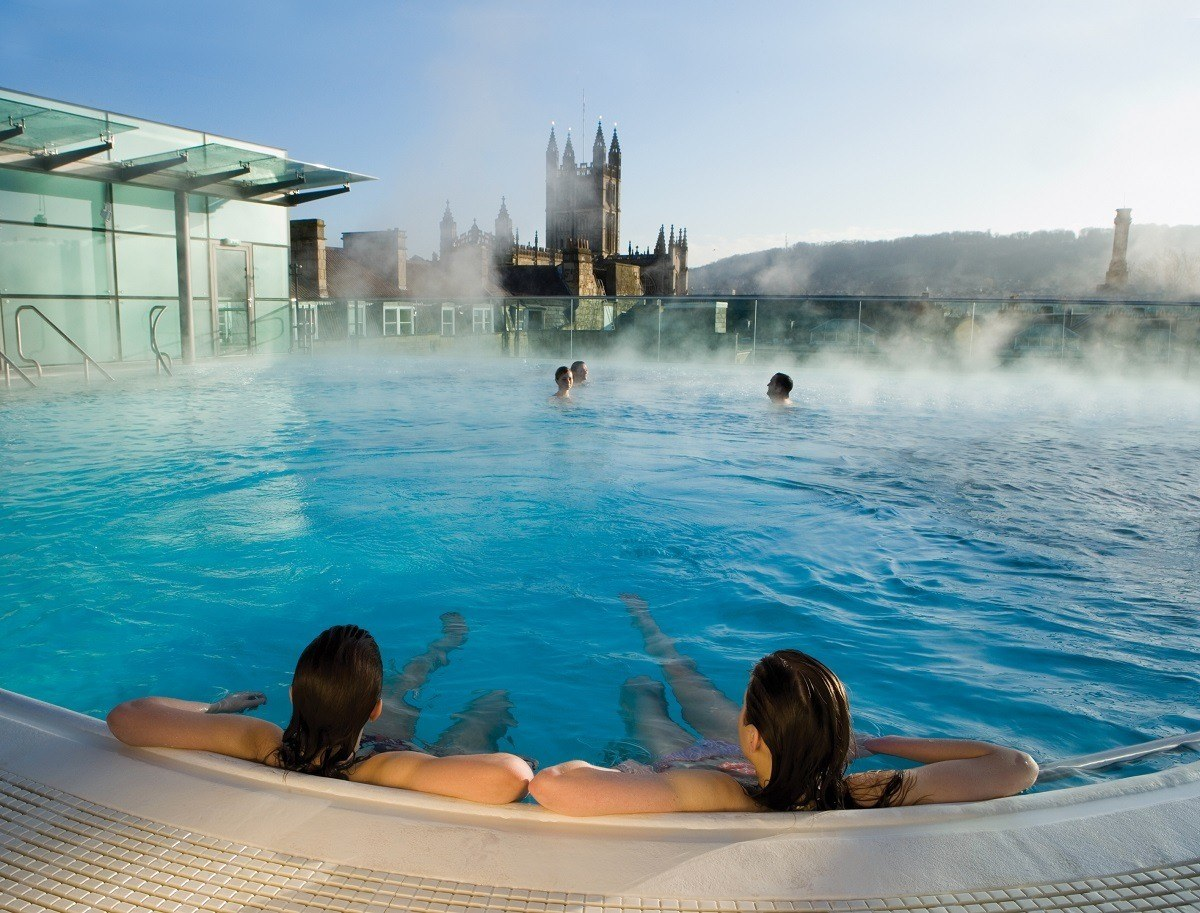 Bathers in the rooftop pool at the Thermae Spa with Bath Abbey in the distance