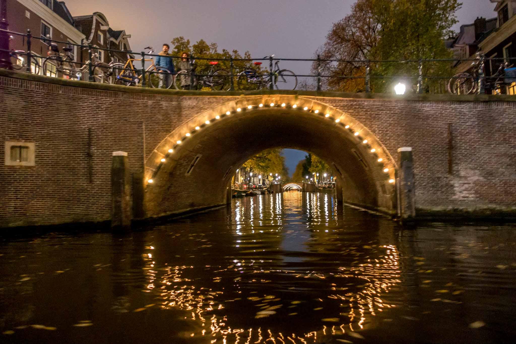 Illuminated bridge over a canal at night
