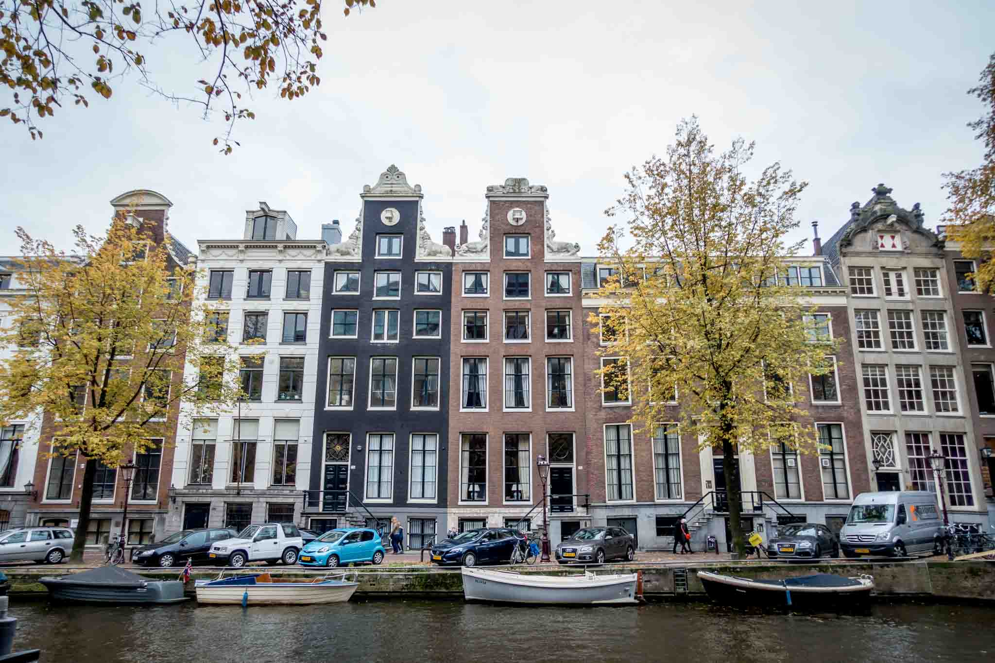 Historic canal houses along a boat-filled canal