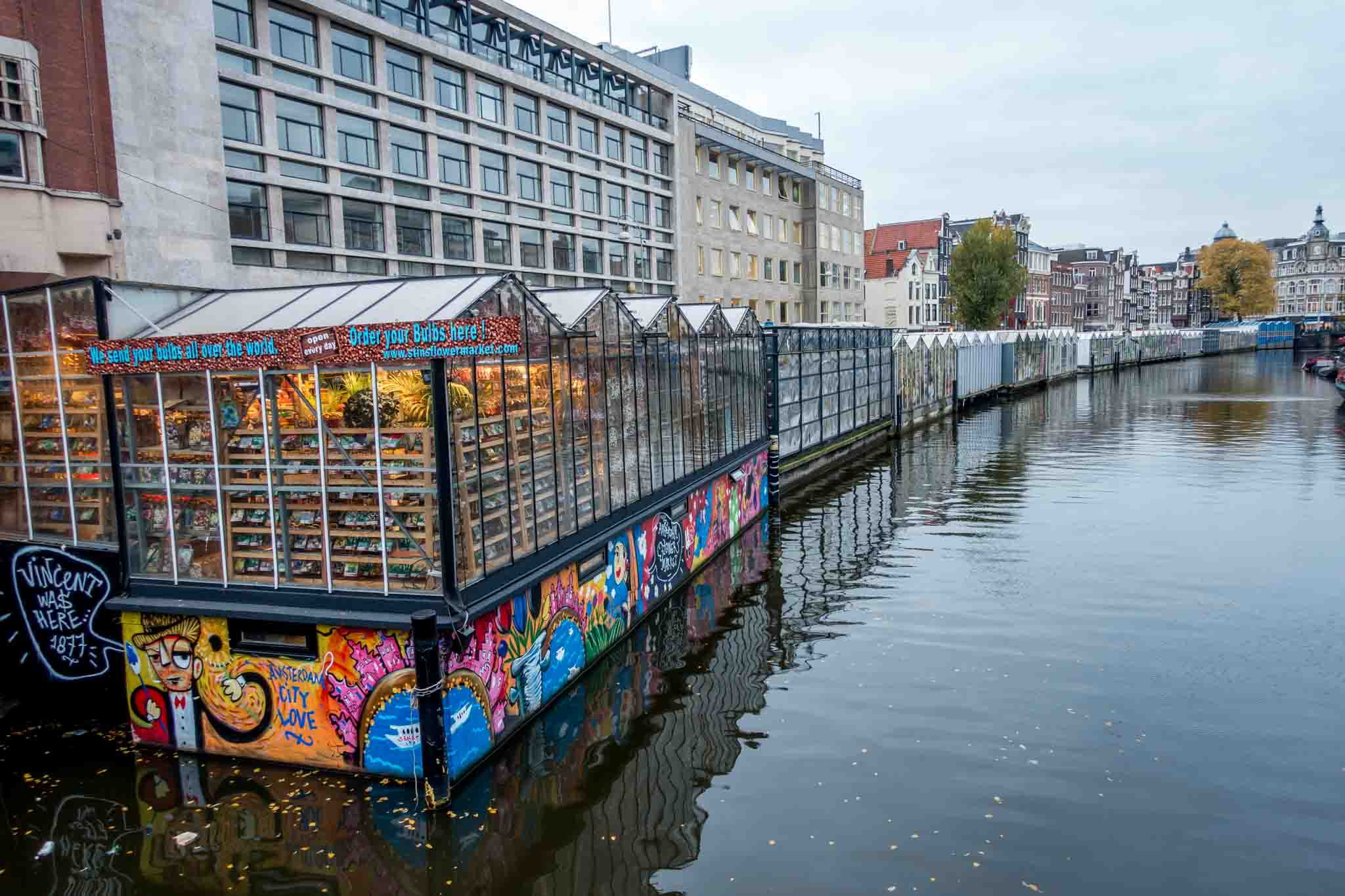 Floating glass booths in a canal comprise the flower market