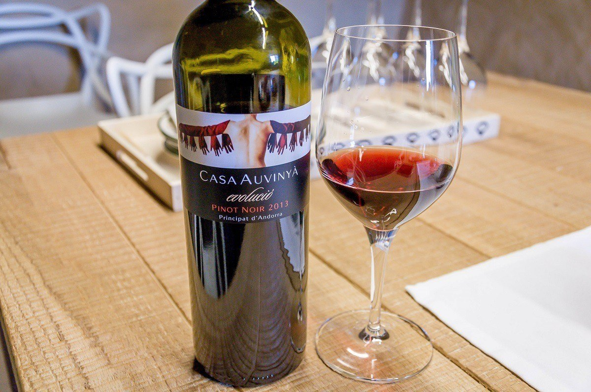Glass and bottle of wine at Casa Auvinya winery on wood table