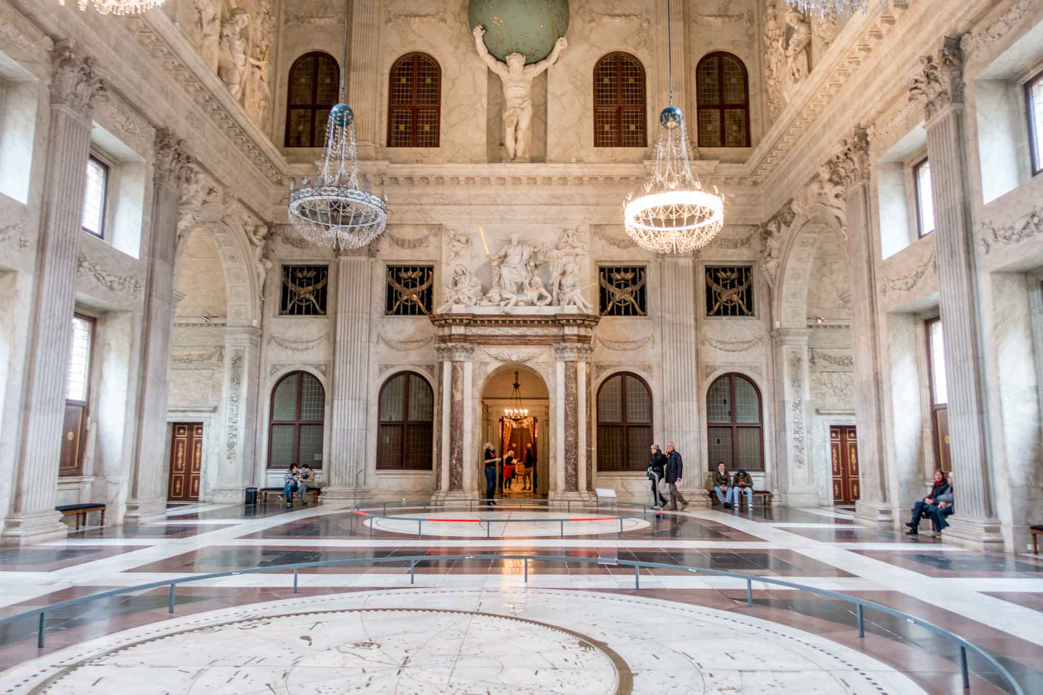Central Hall with white marble work and sculpture of Atlas holding a globe