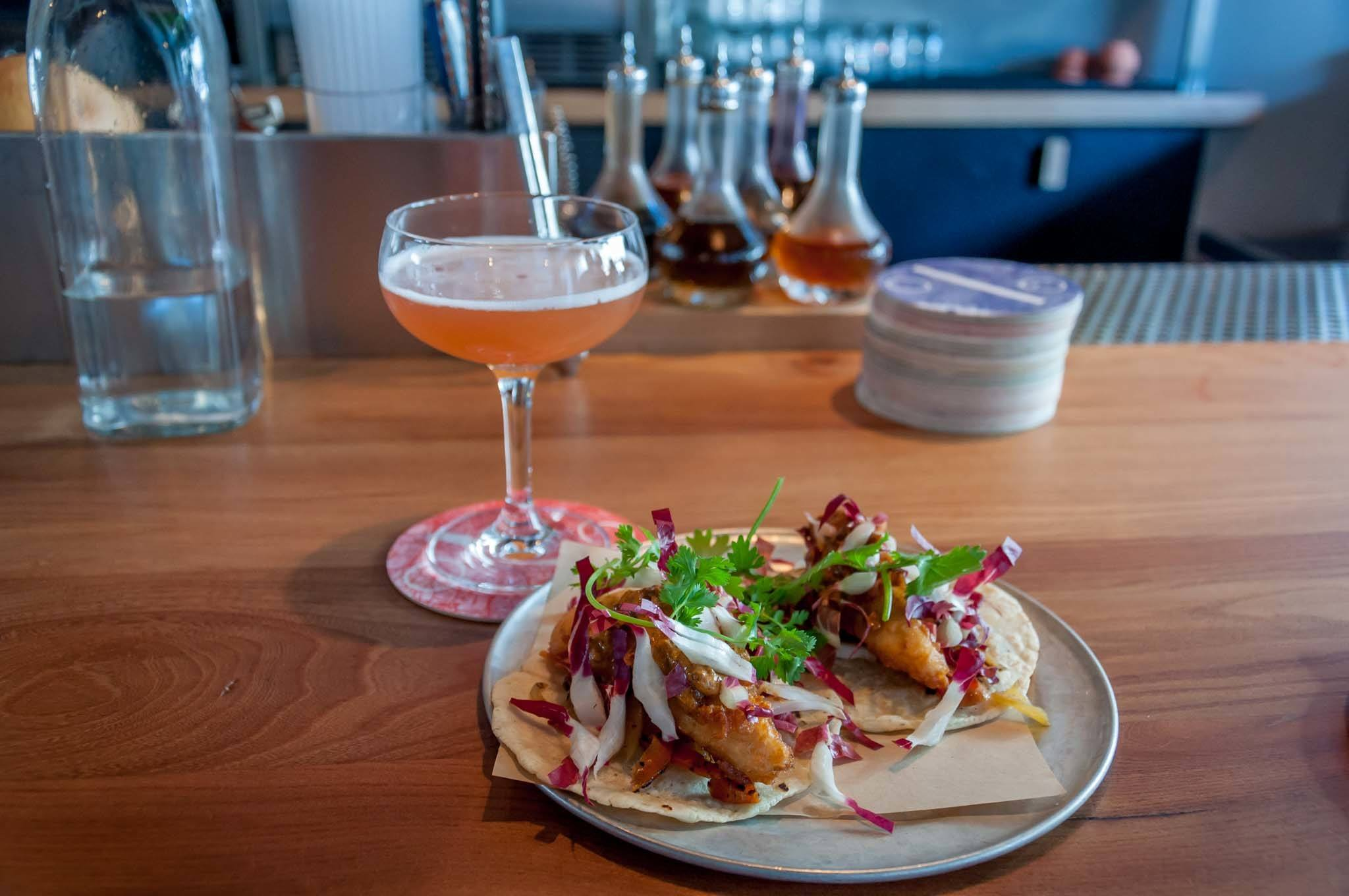Cocktail and fish tacos on a table