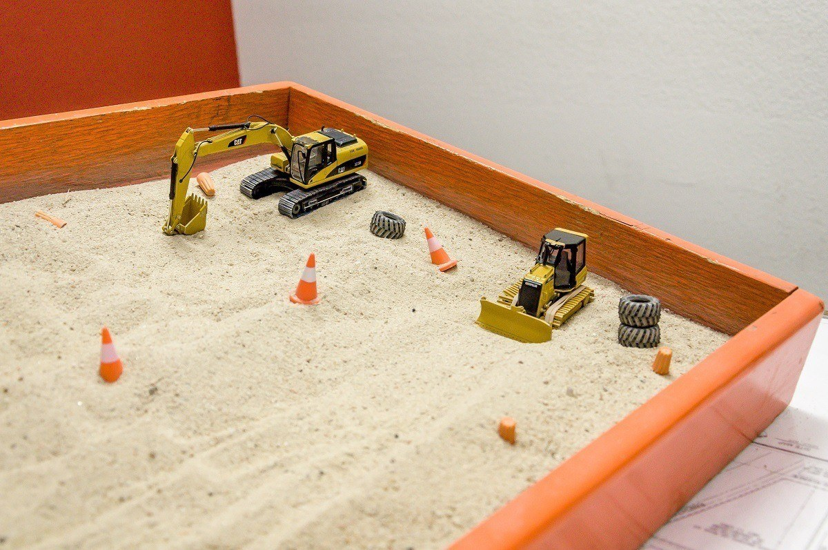Construction equipment in a sandbox for a safety demonstration model