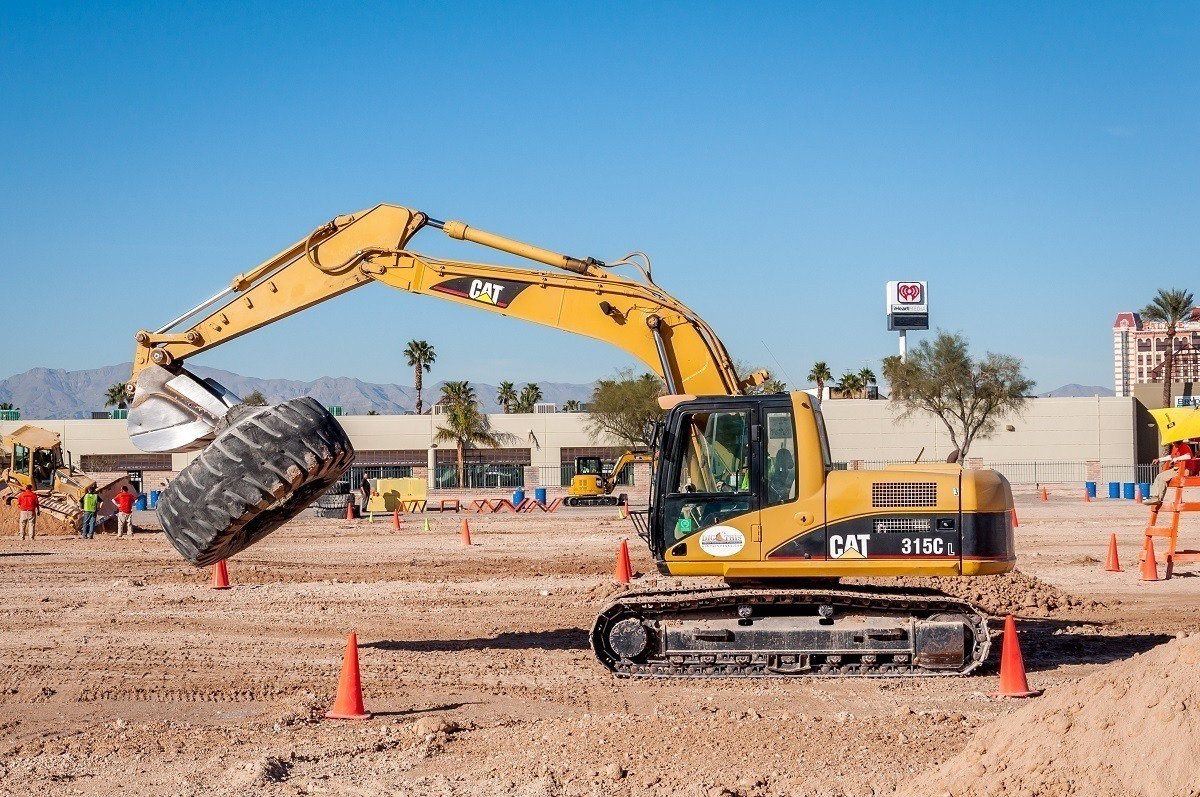 Excavator carrying tires across the sandbox at a construction playground