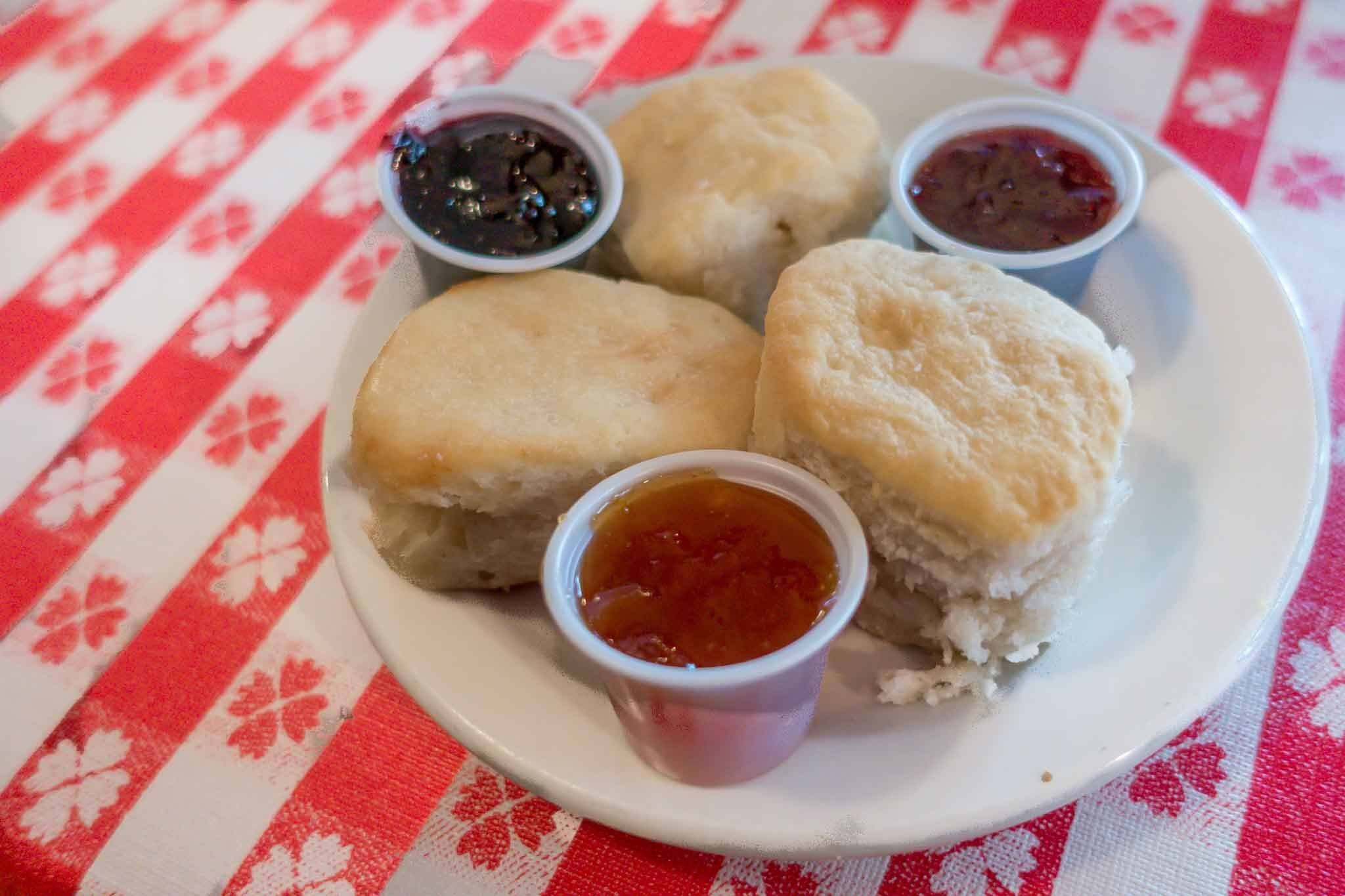 Biscuits on a plate with three kinds of preserves