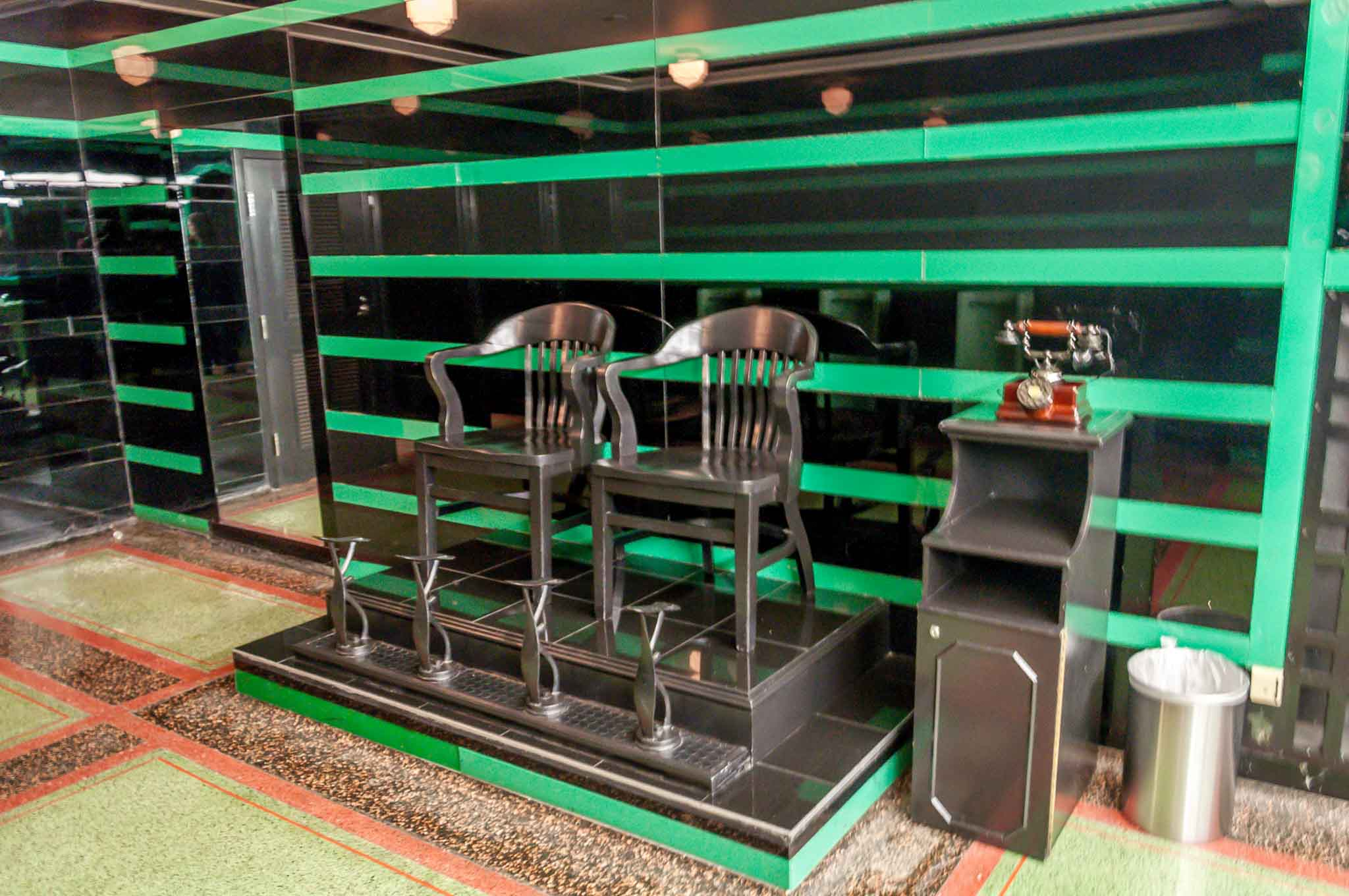 Black chairs in front of black and green wall