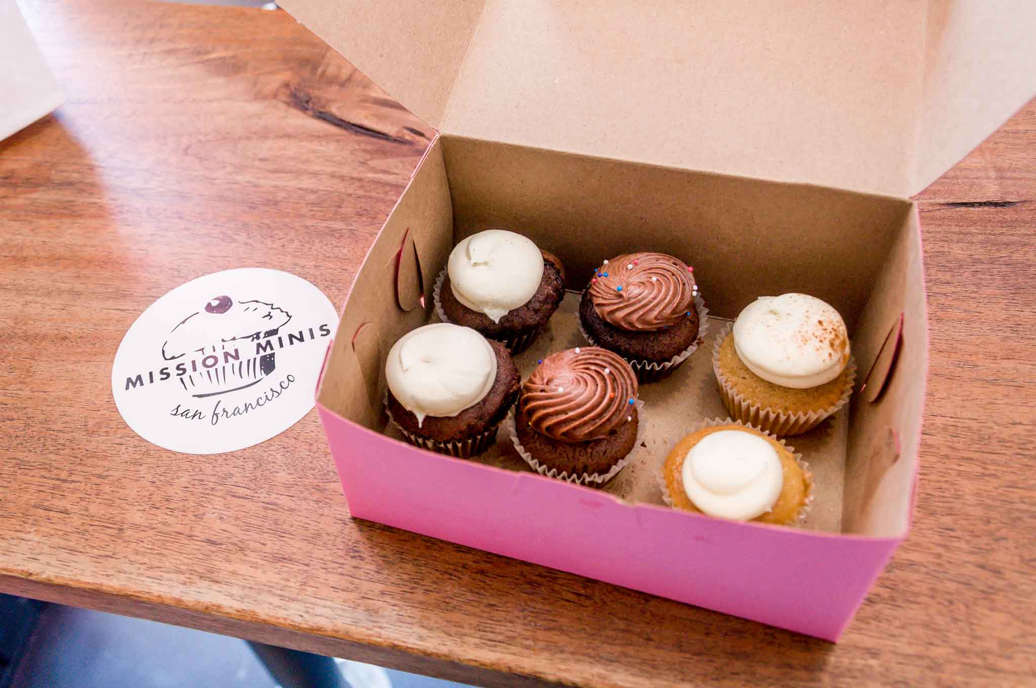 """Box of mini cupcakes beside a """"Mission Minis"""" coaster"""