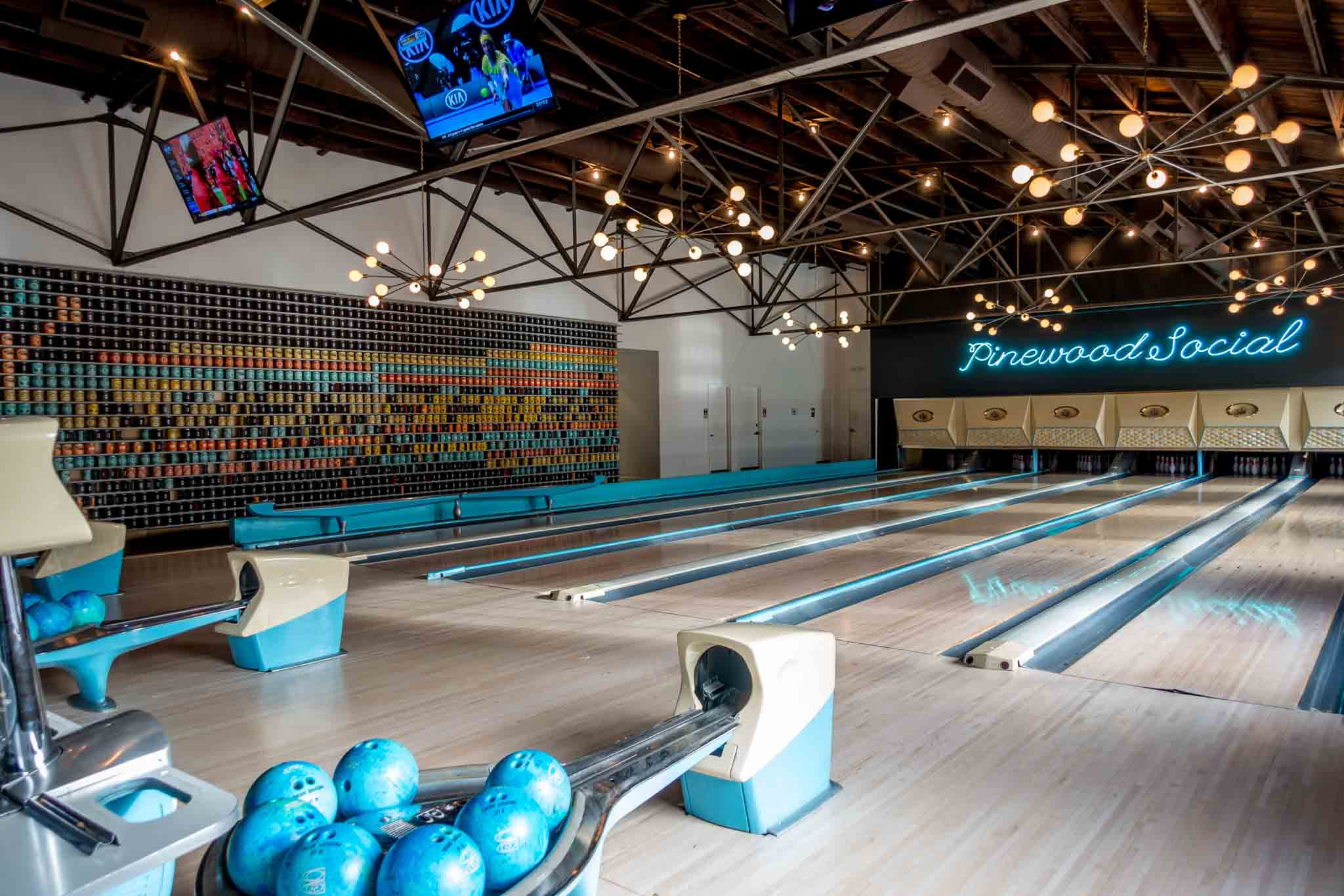 Blue bowling balls in a bowling alley with a sign for Pinewood Social