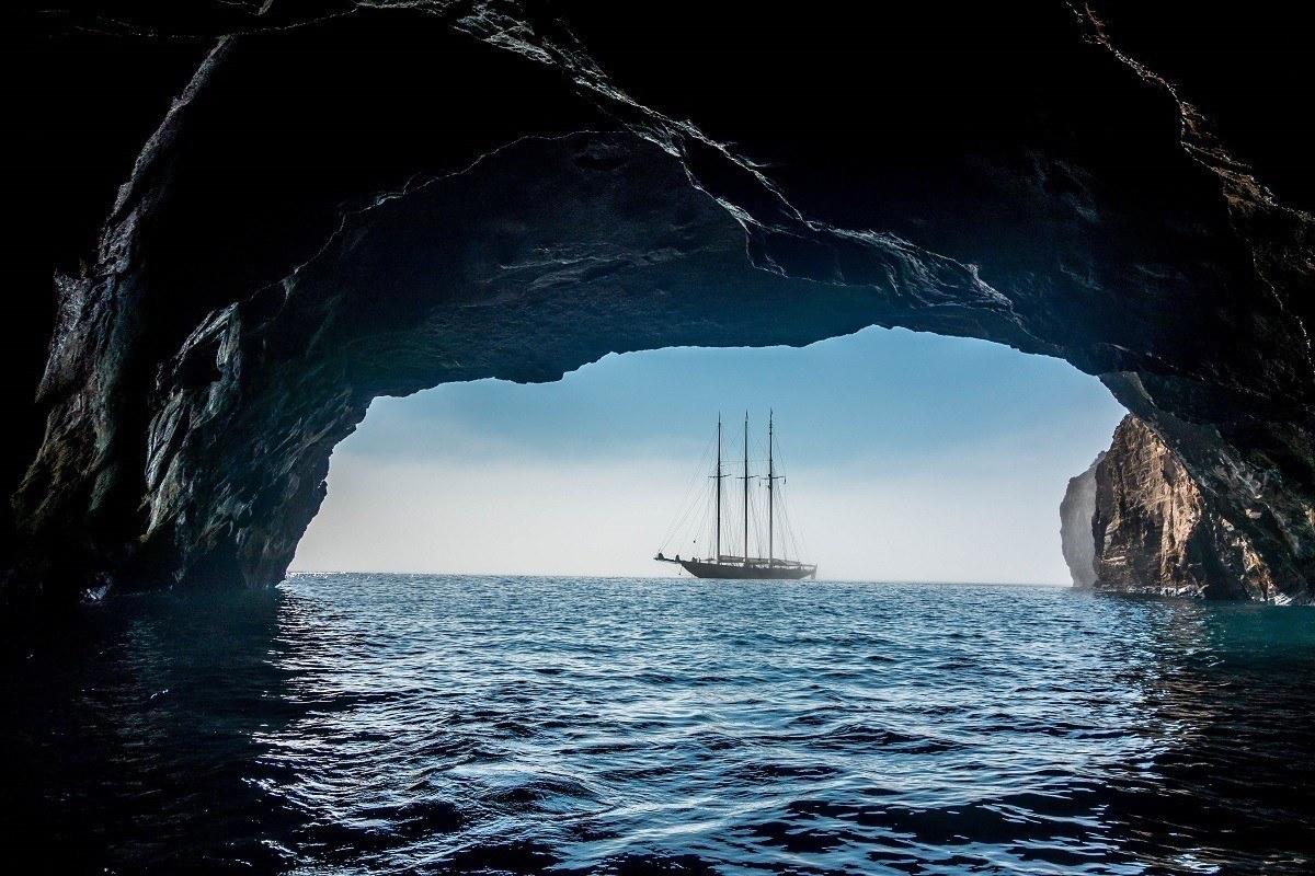 Ship seen through the arch of a cave