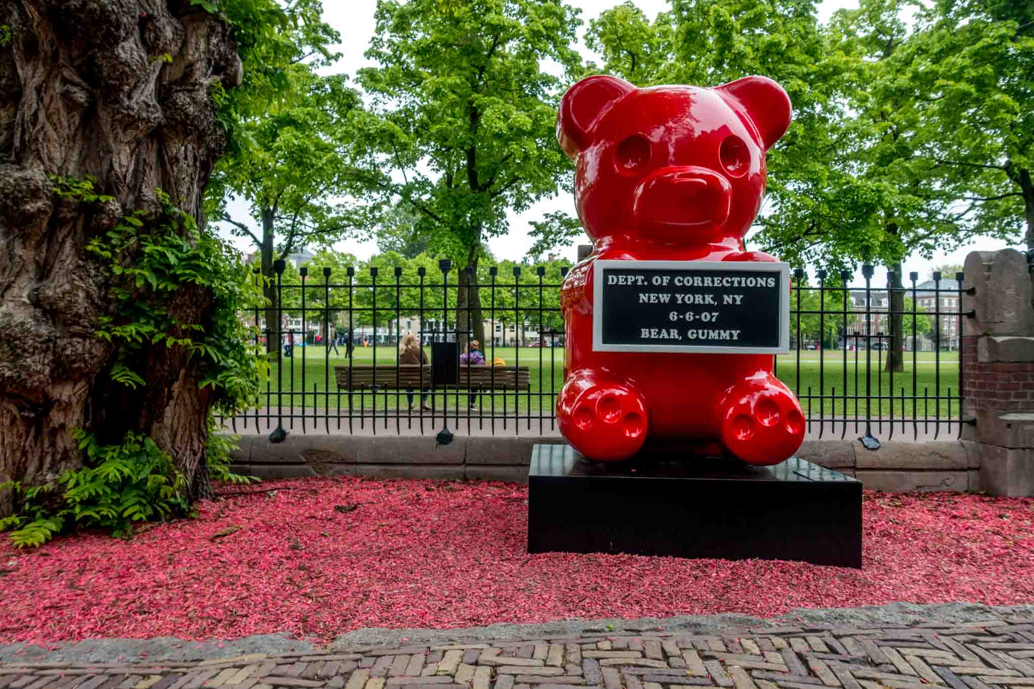 Red gummy bear statue holding a mug shot plaque