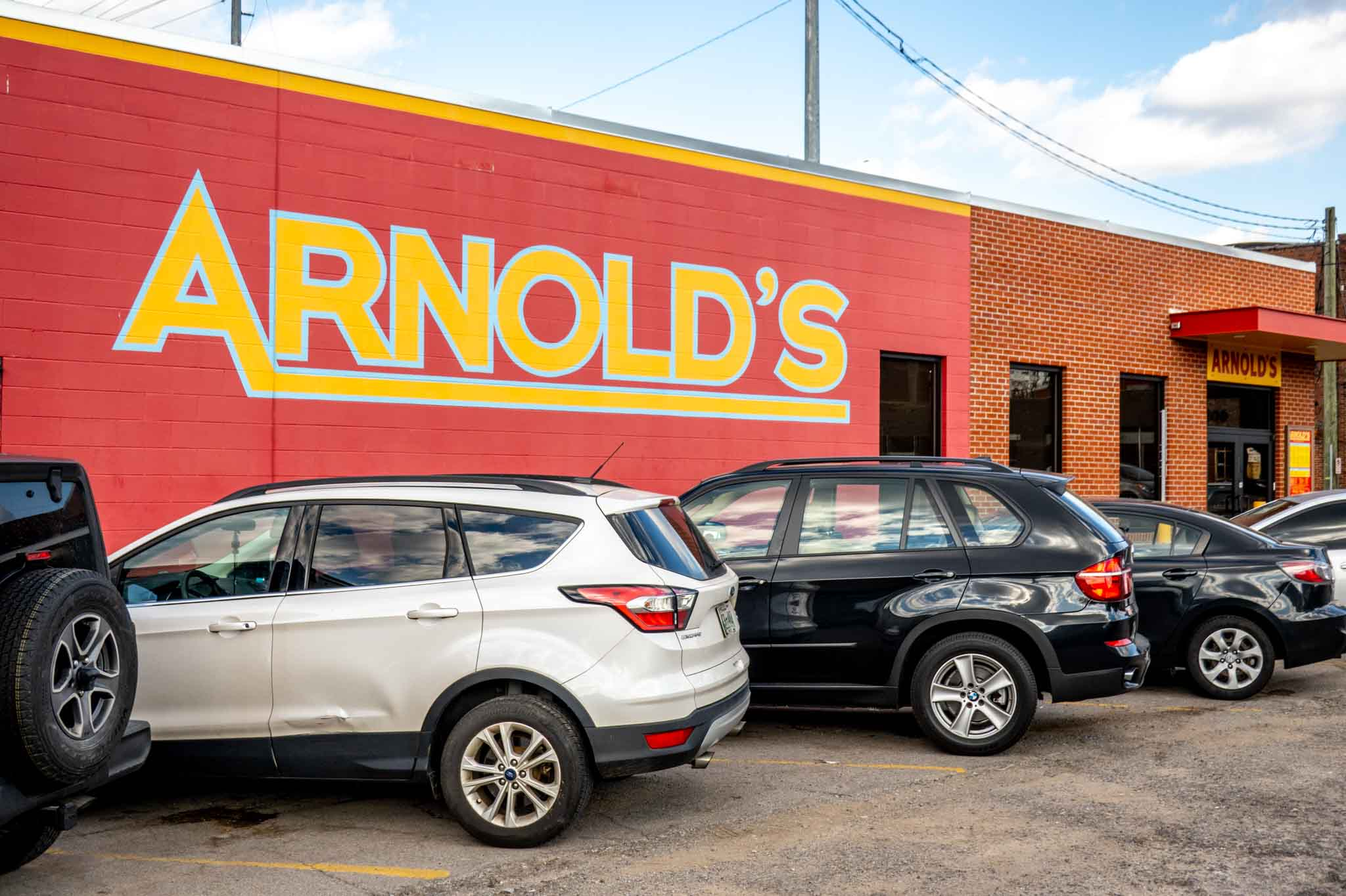 Yellow and red sign for Arnold's restaurant pained on a brick wall