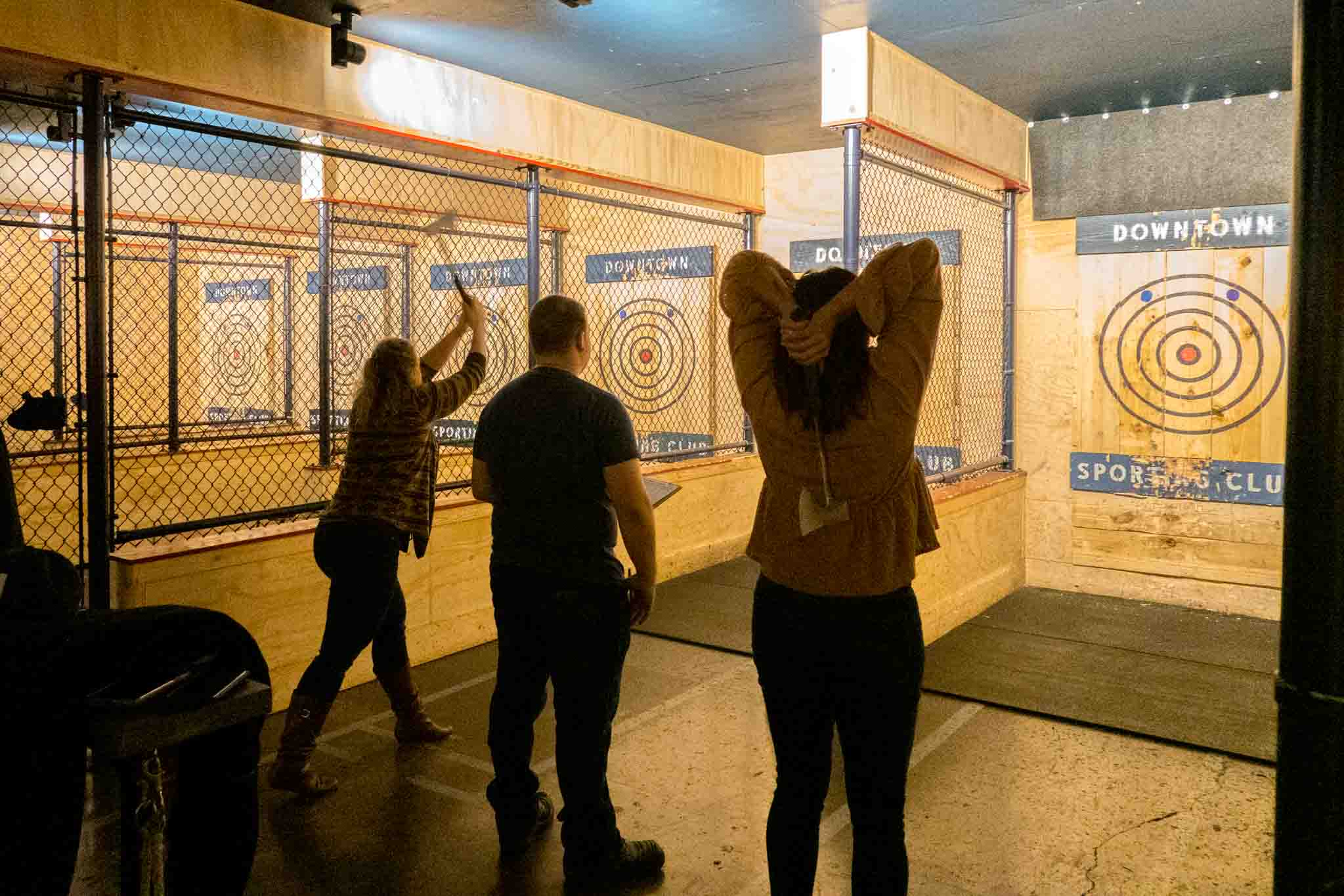 Two people throwing axes at targets on a wall
