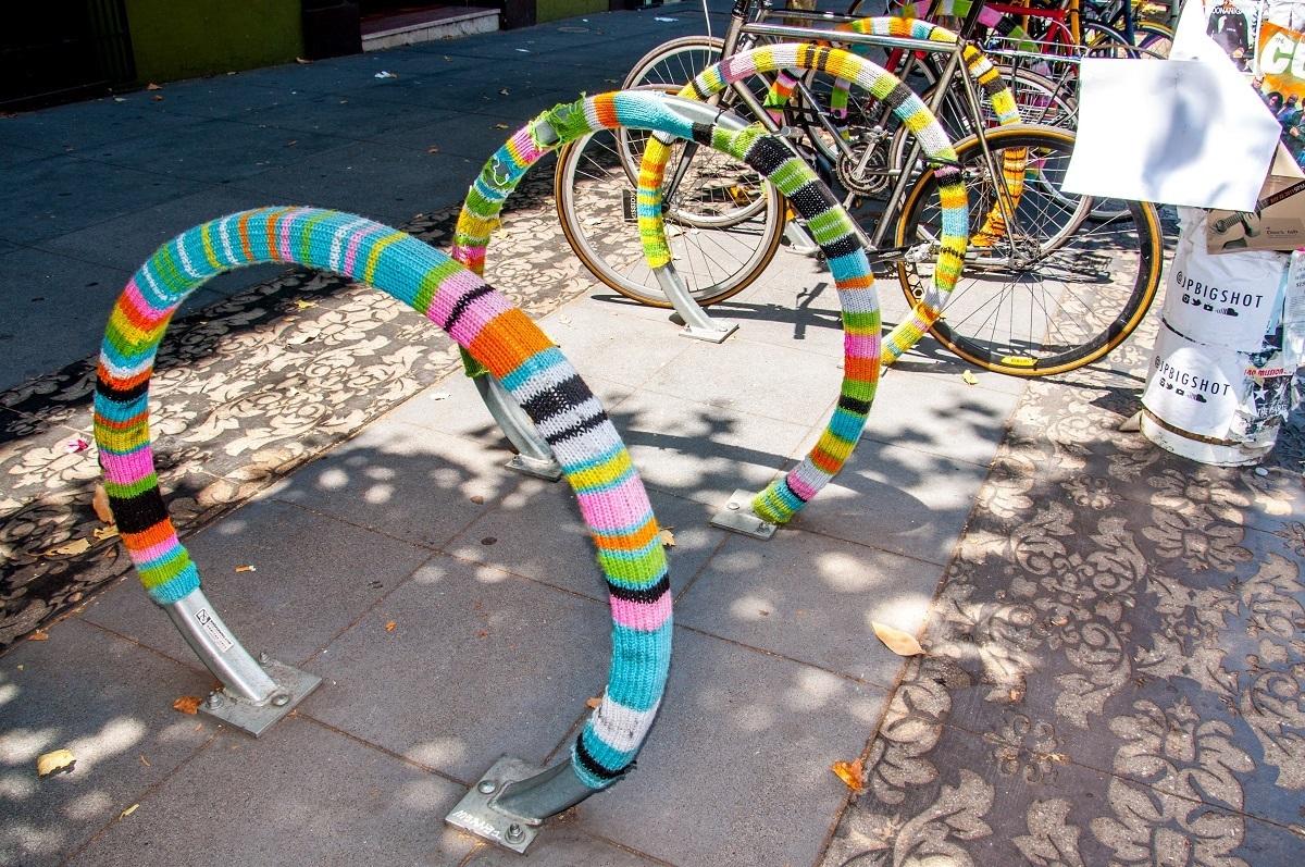 Bike rack covered in multi-colored yarn