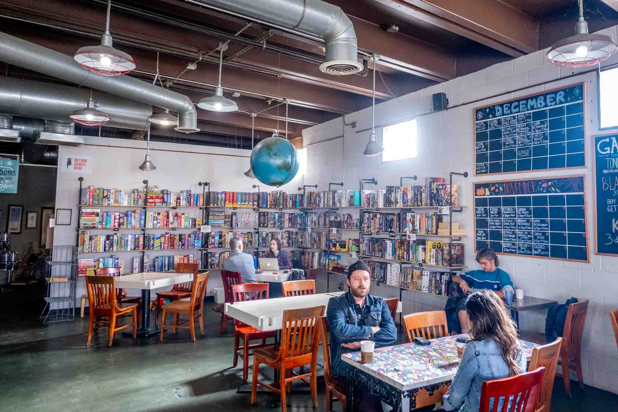 People at tables by a wall of board games