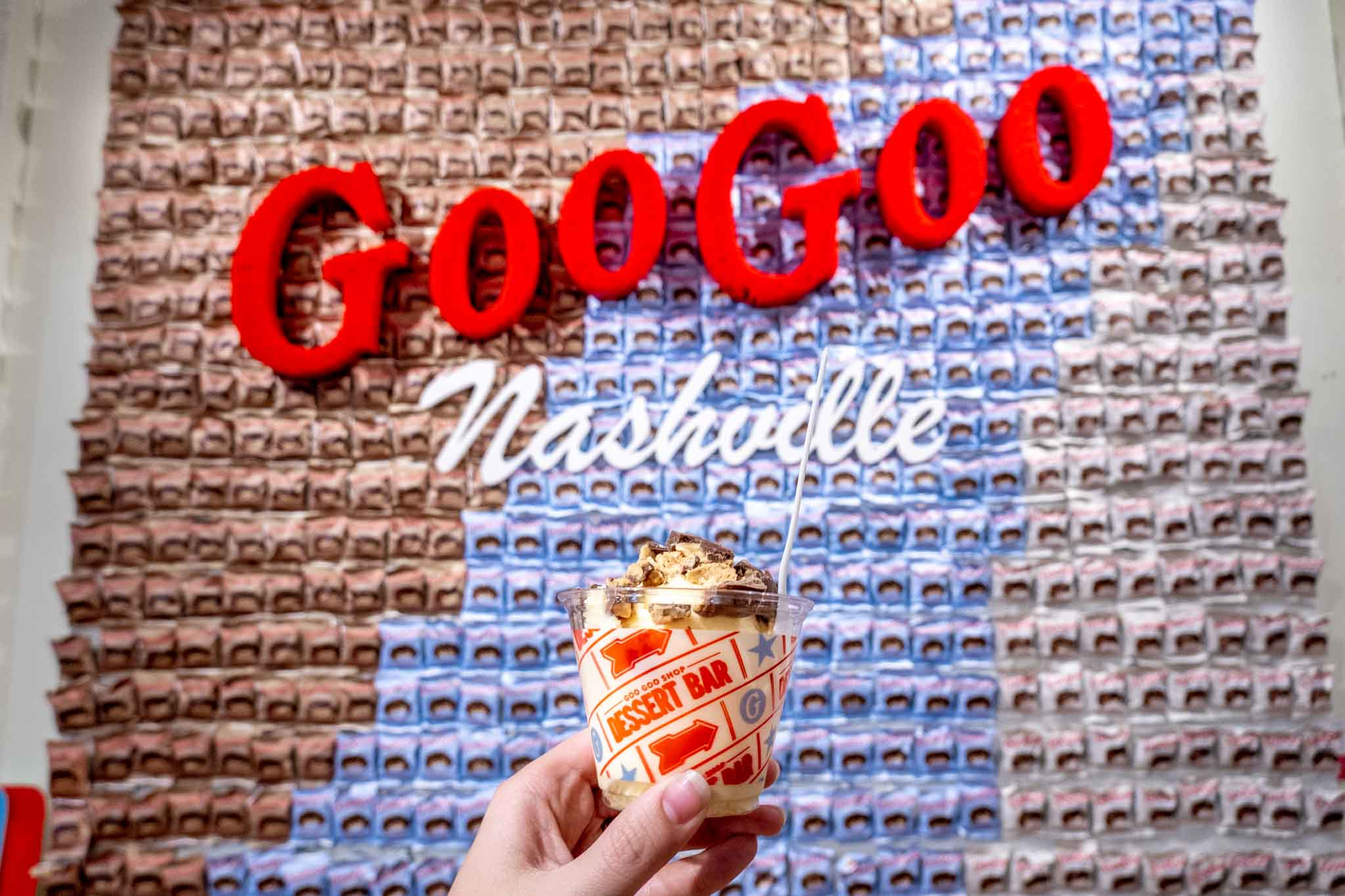Ice cream topped with Goo Goo Clusters in front of decorated wall