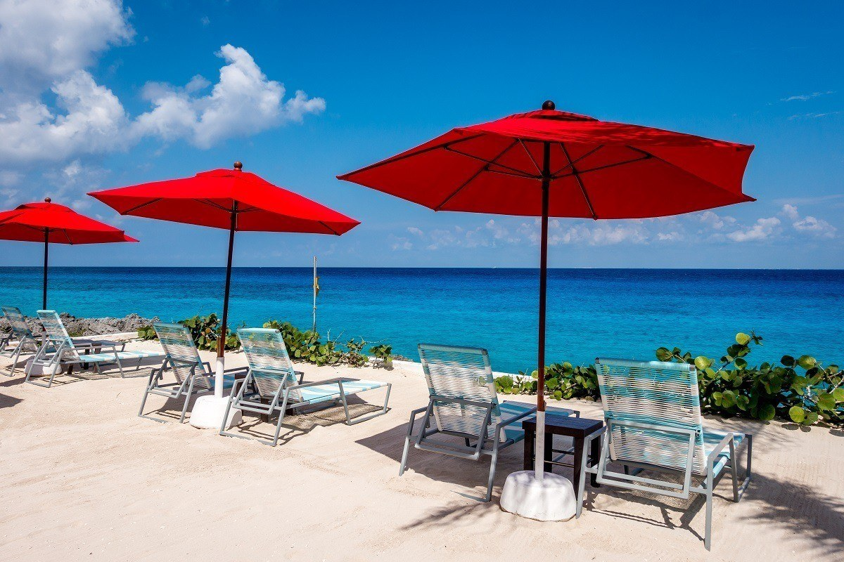 Beach chairs on the beach in Mexico with red umbrellas