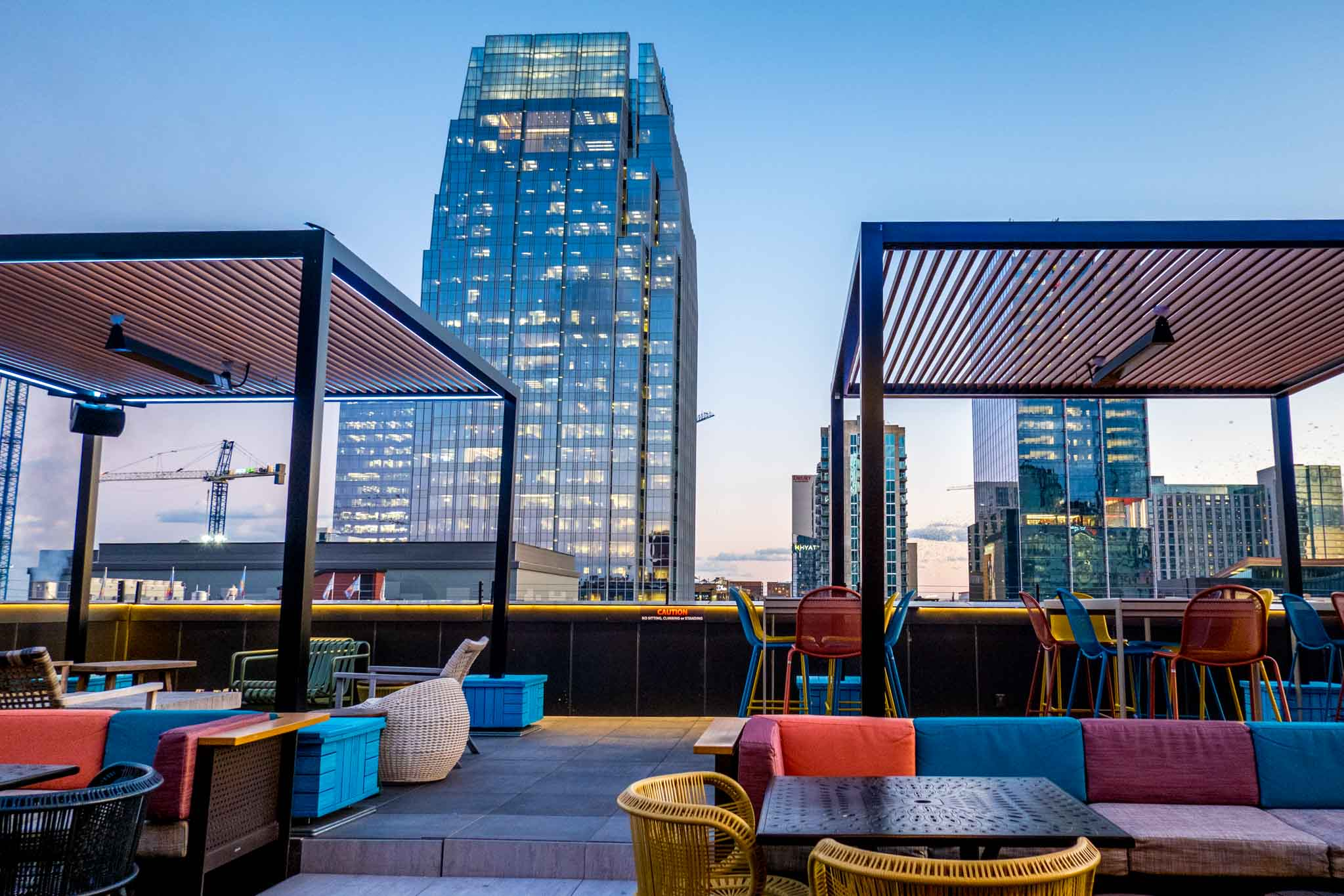 Rooftop bar at sunset featuring seats and a view over Broadway