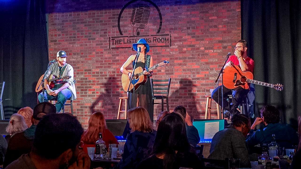 Three guitar players seated on stage at The Listening Room Cafe