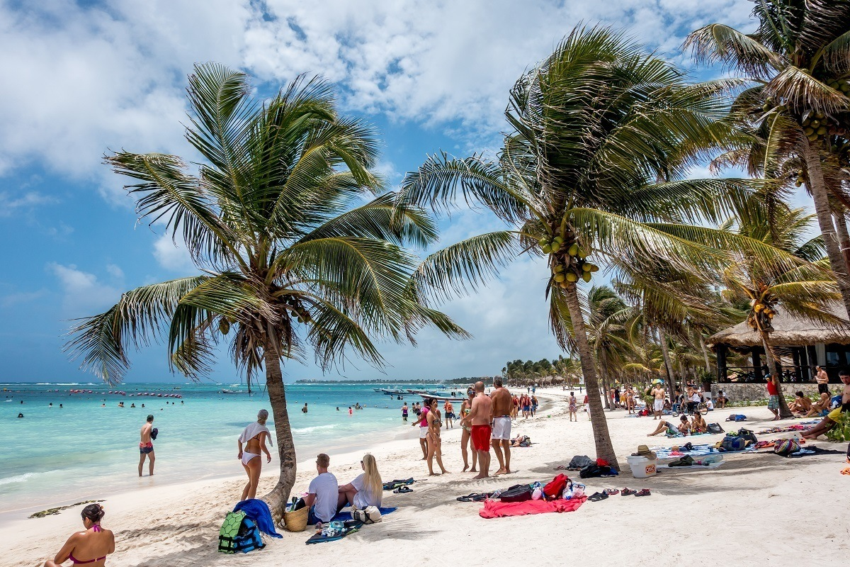 People under palm trees on Akumal beach Mexico
