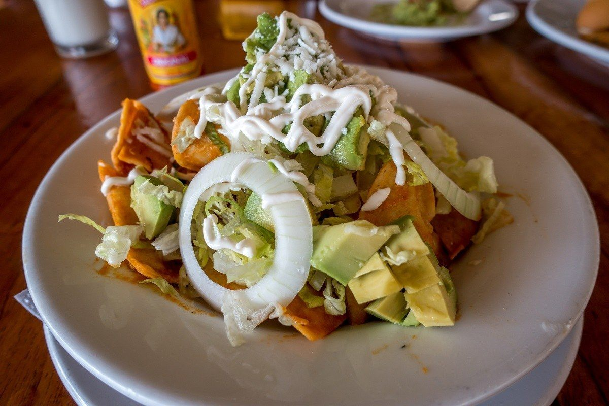 Chilaquiles topped with avocado on a plate