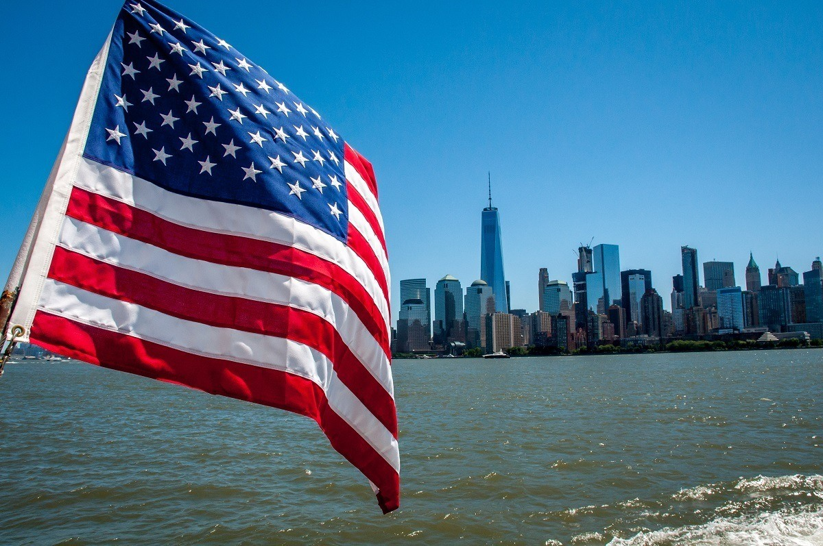 An American flag flying with the New York skyline in the background